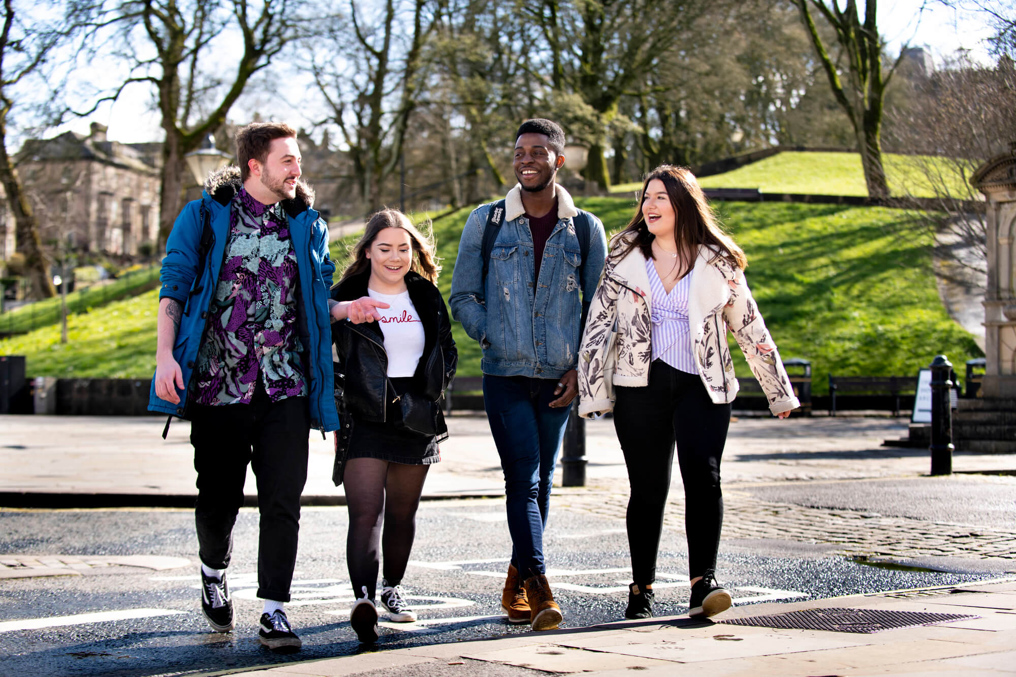 Four University of Derby students walk through the streets of Buxton town on a bright day.  Tow girls and two boys, dressed in casual clothes of denim, skirts, tshirts, boots and trainers.  Green grass and trees appear in the near distance showing Spring has arrived.