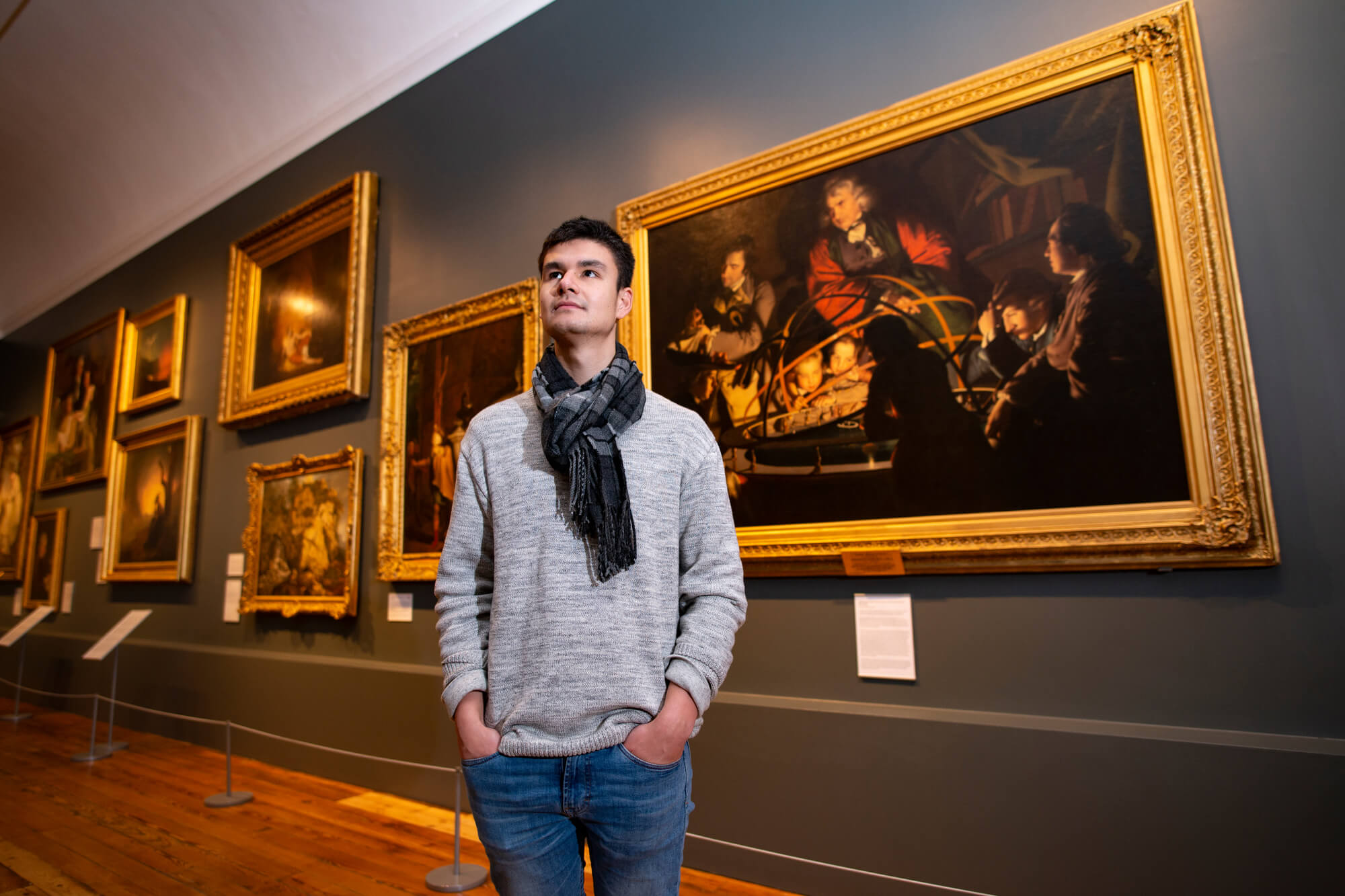 A male student looking at Joseph Wright paintings at Derby Museum and Art Gallery