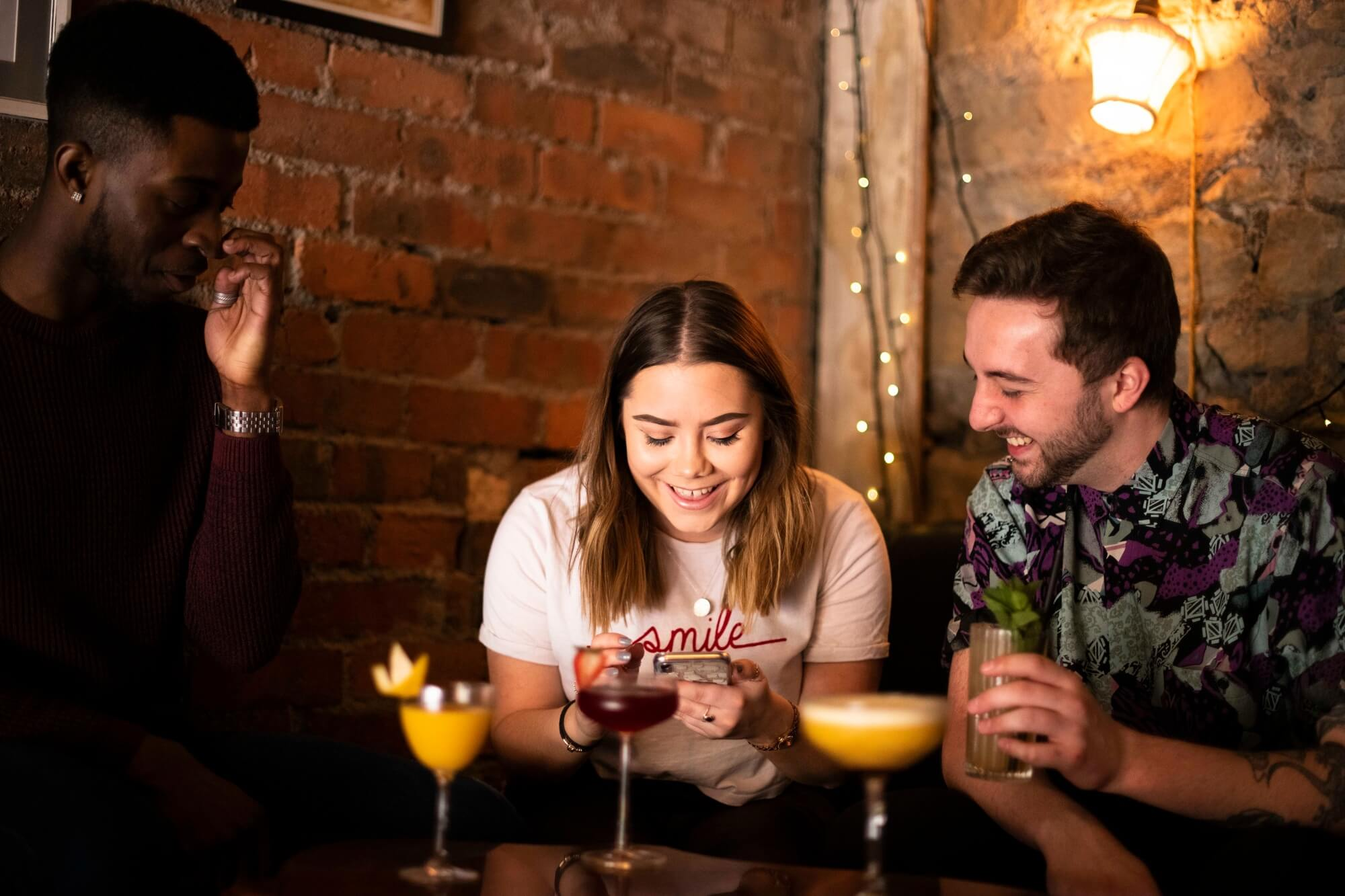 Three University of Derby students sit in bar drinking cocktails laughing in each others company