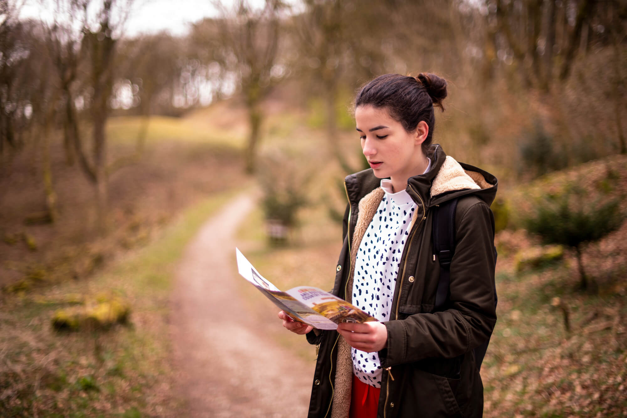 A University of Derby student looks at a tour guide map in the trails of the Peak District.  Wearing a fur lined hooded coat, bright red trousers and black and white jumper she looks relaxed and at peace.