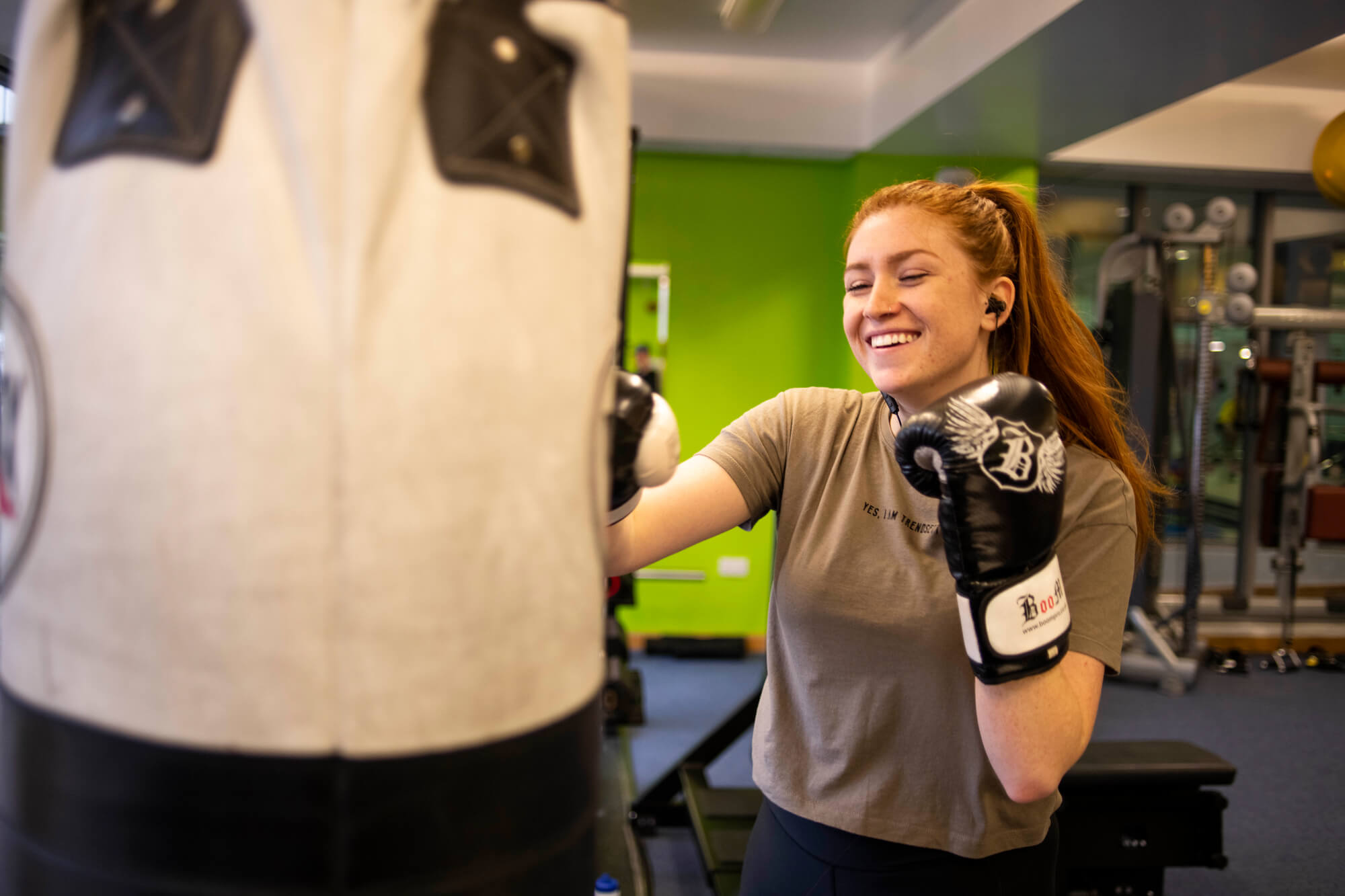 A University of Derby student with long red hair tied in a ponytail, wearing a khaki green tshirt and boxing gloves, smiles as she punches a boxing bag