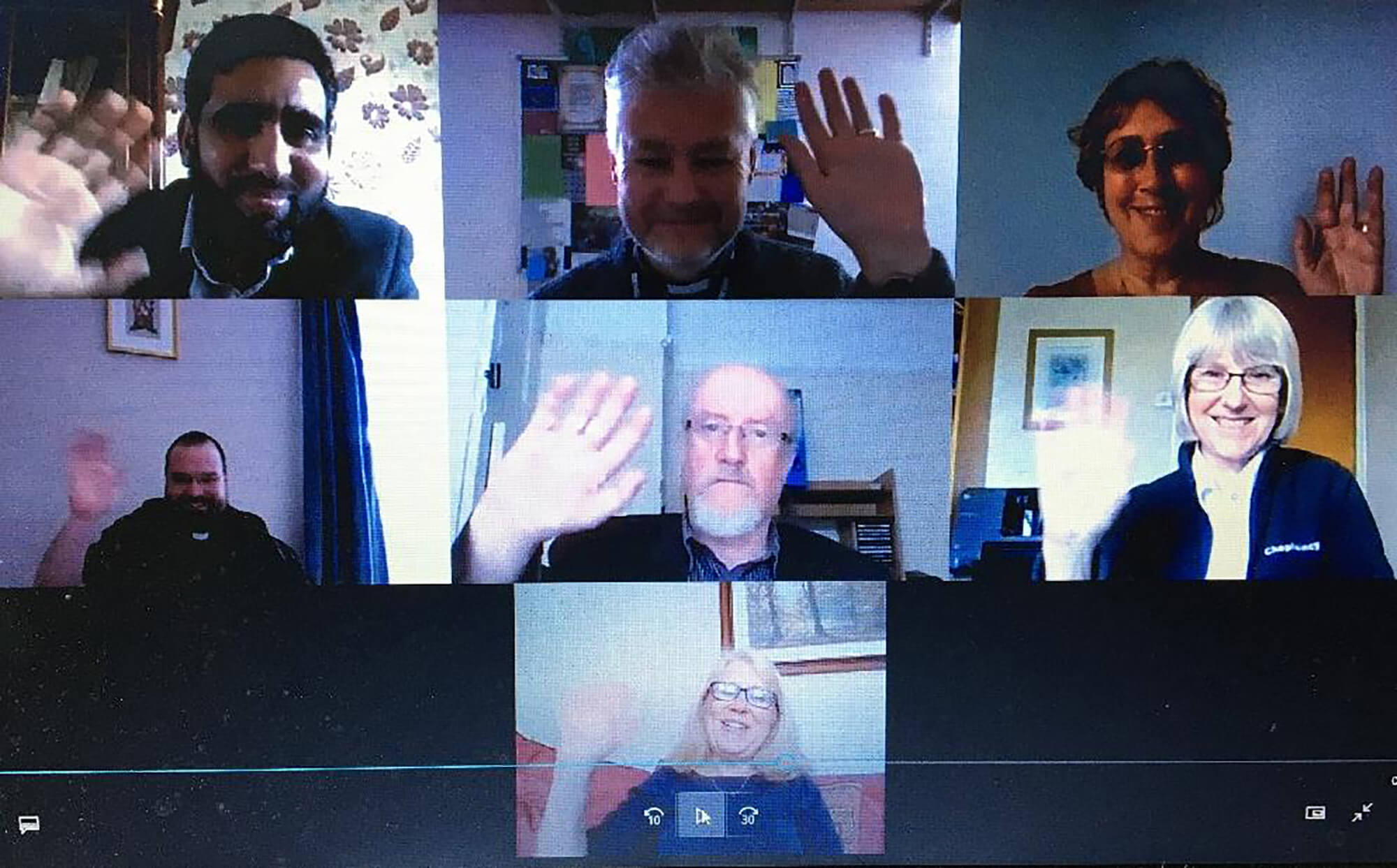 Seven people meeting remotely via a video conferencing platform