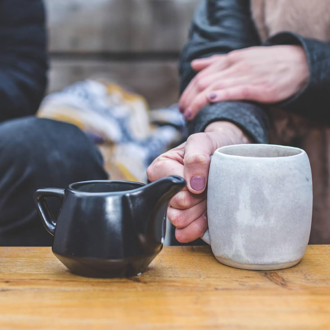 two people sitting down having cup of tea