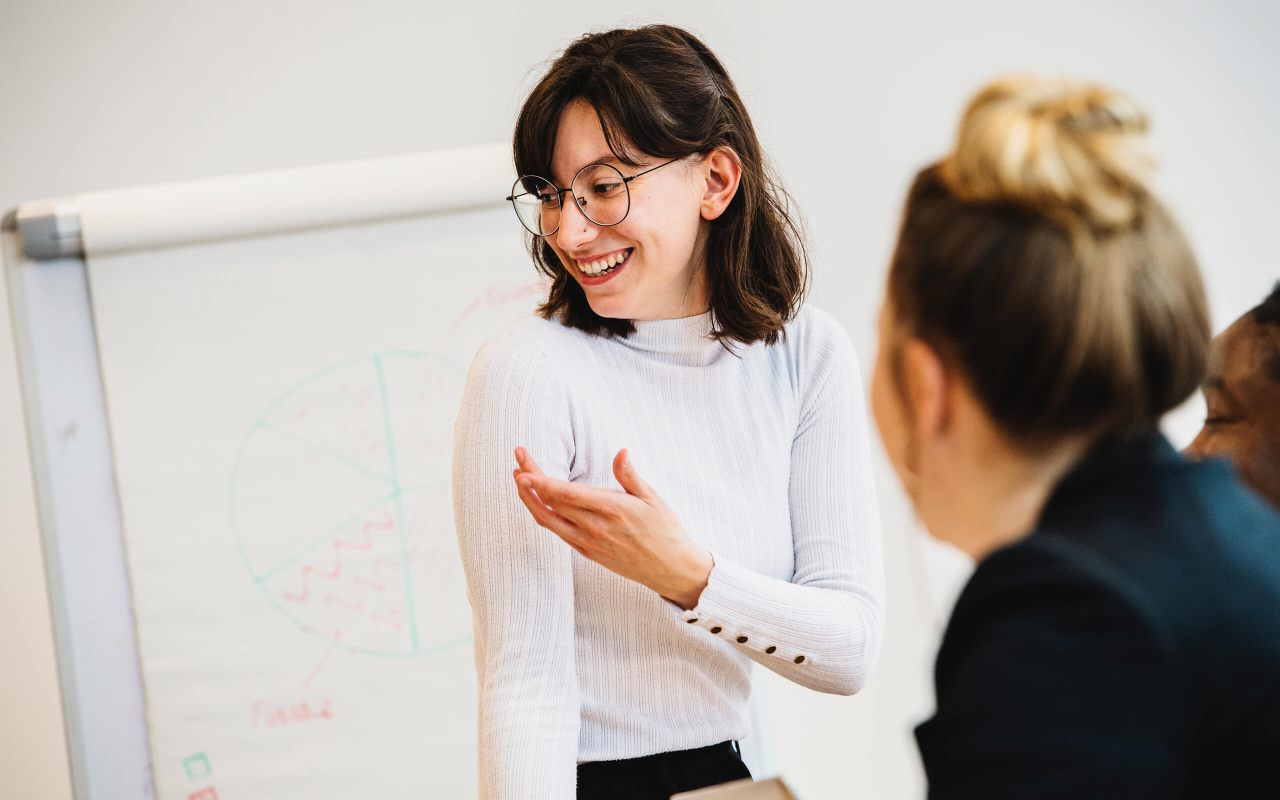 female student in white tshirt talking to other students