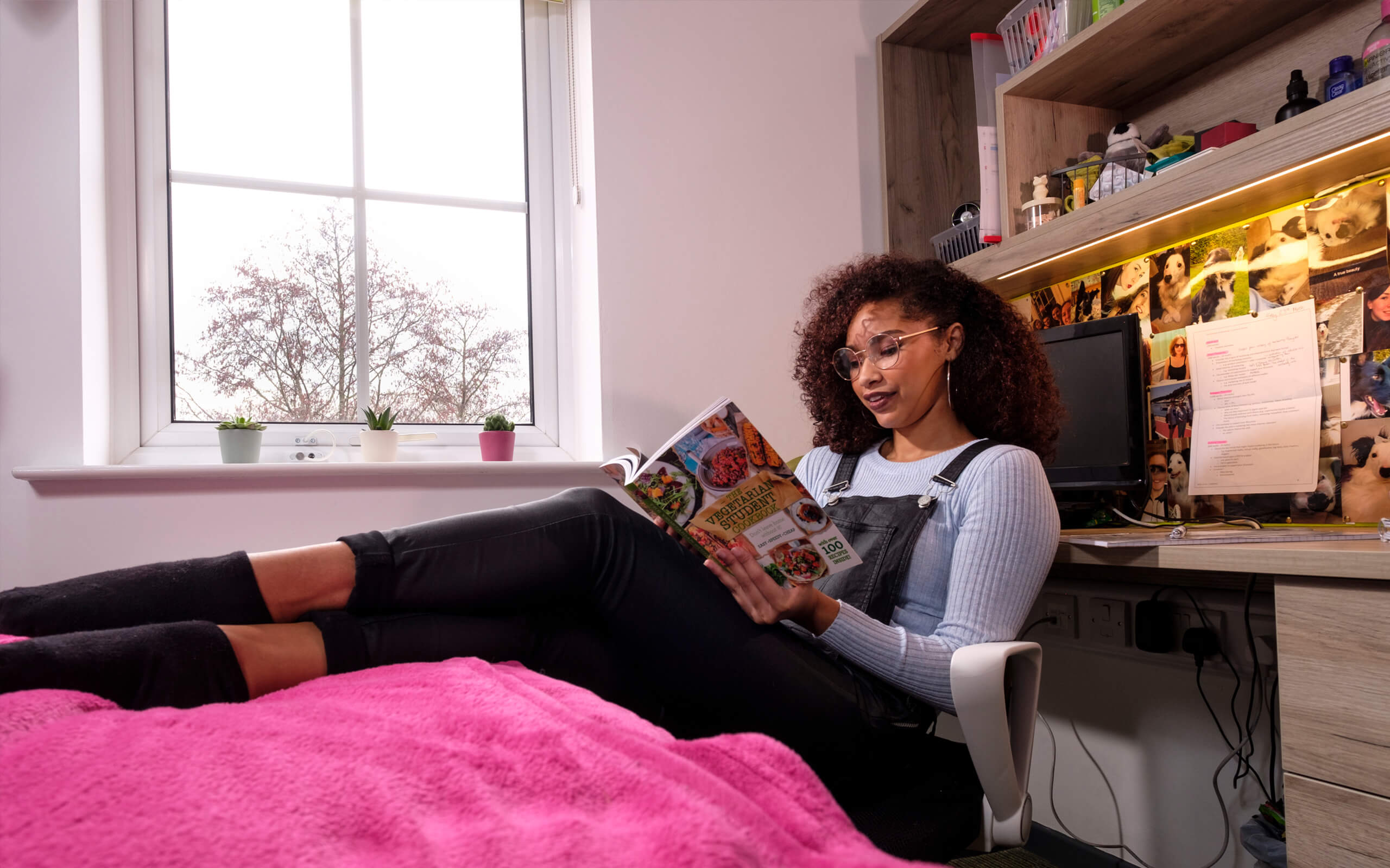 A female student reading in her halls bedroom