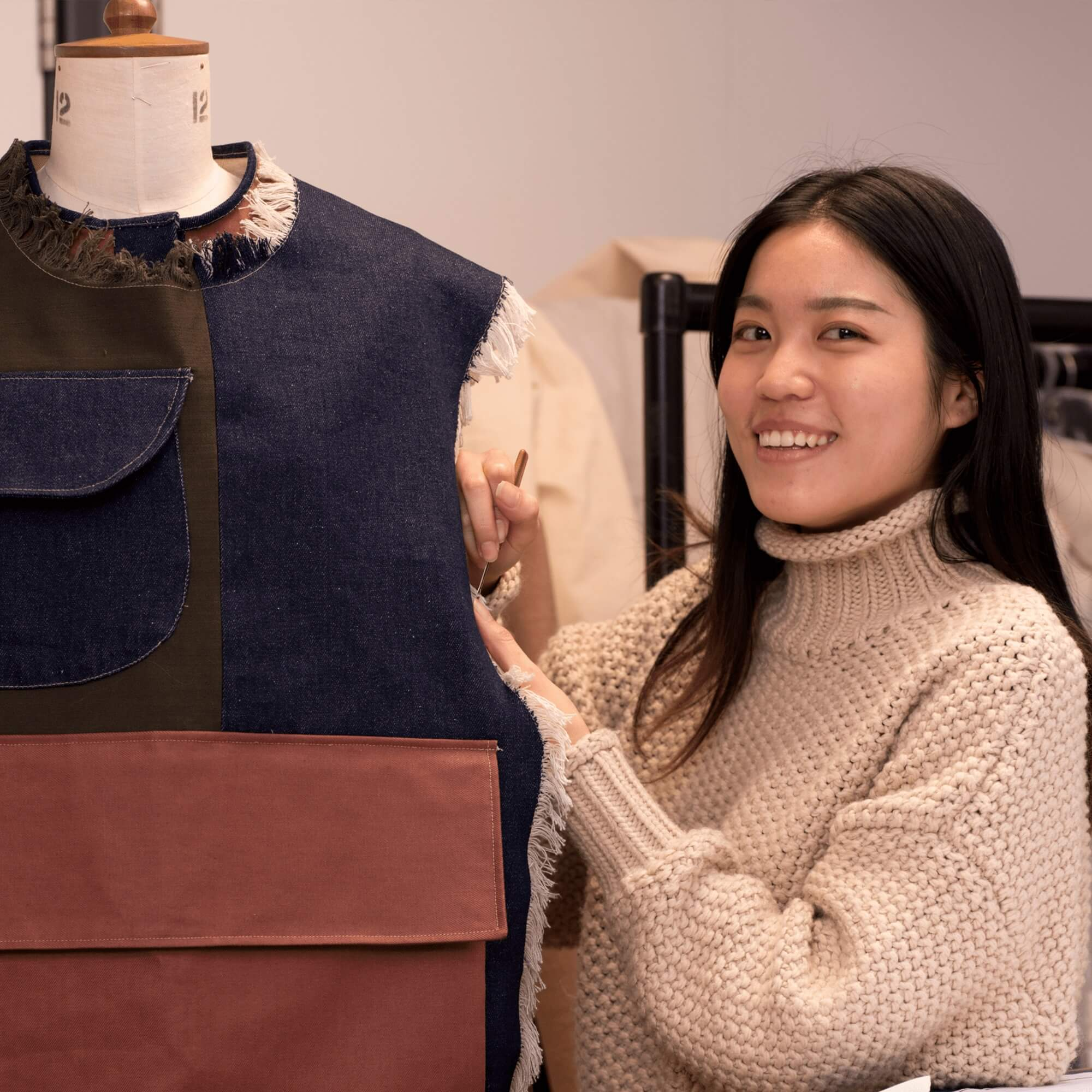 A international student beside her fashion course project work