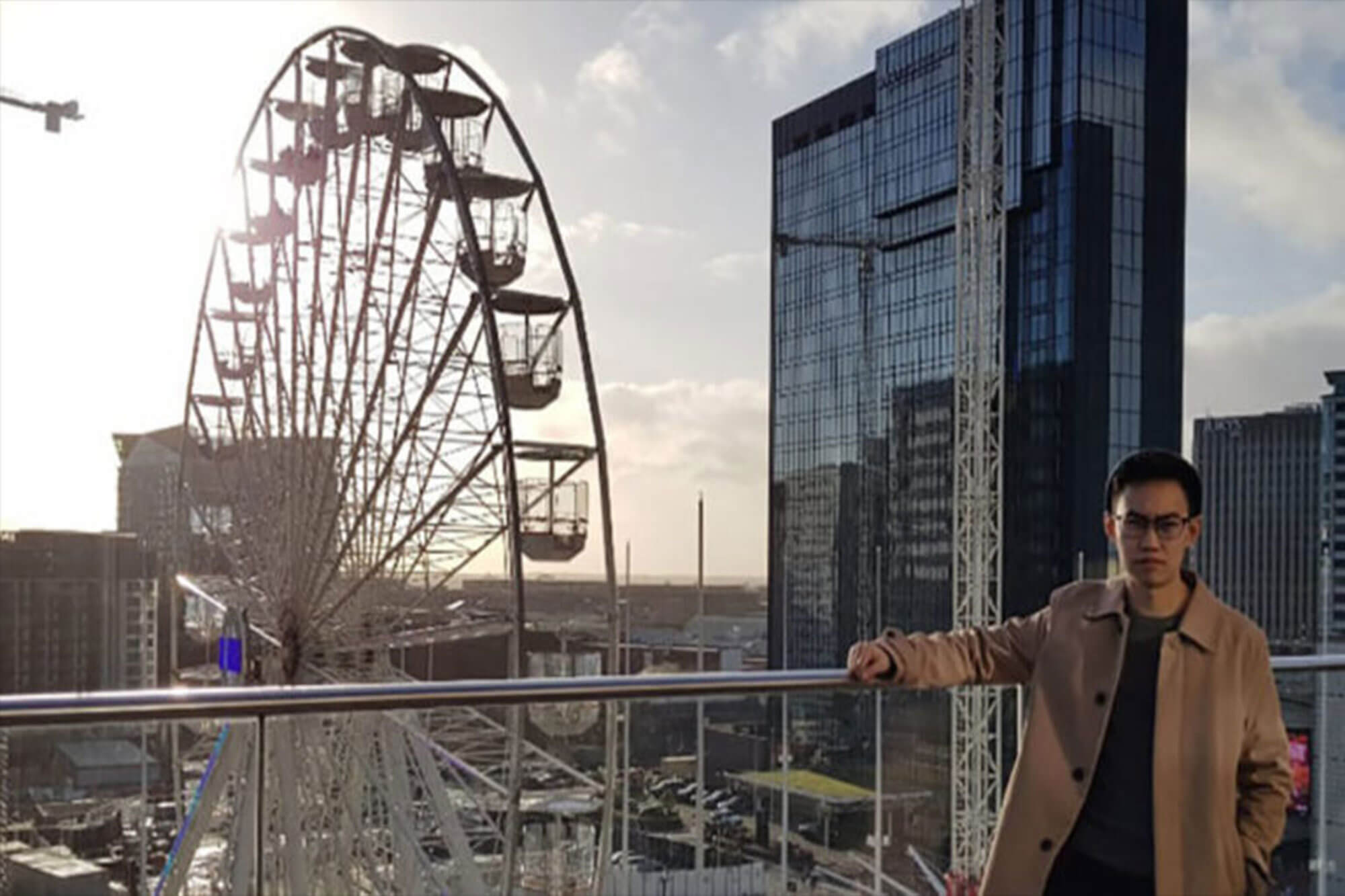 International student in a city centre with Ferris wheel in the background
