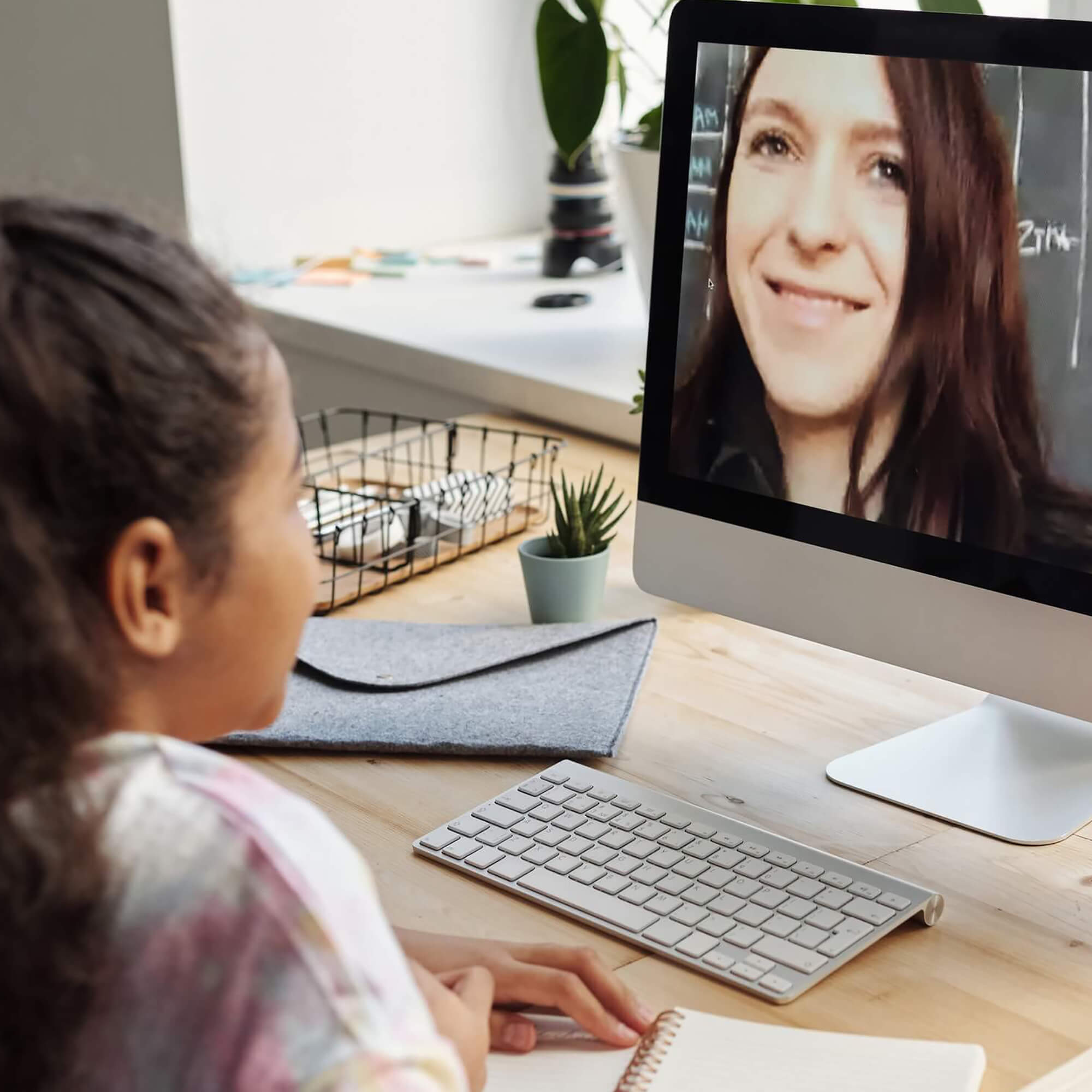 Person sitting at table looking at a computer monitor, talking to a person on the screen.