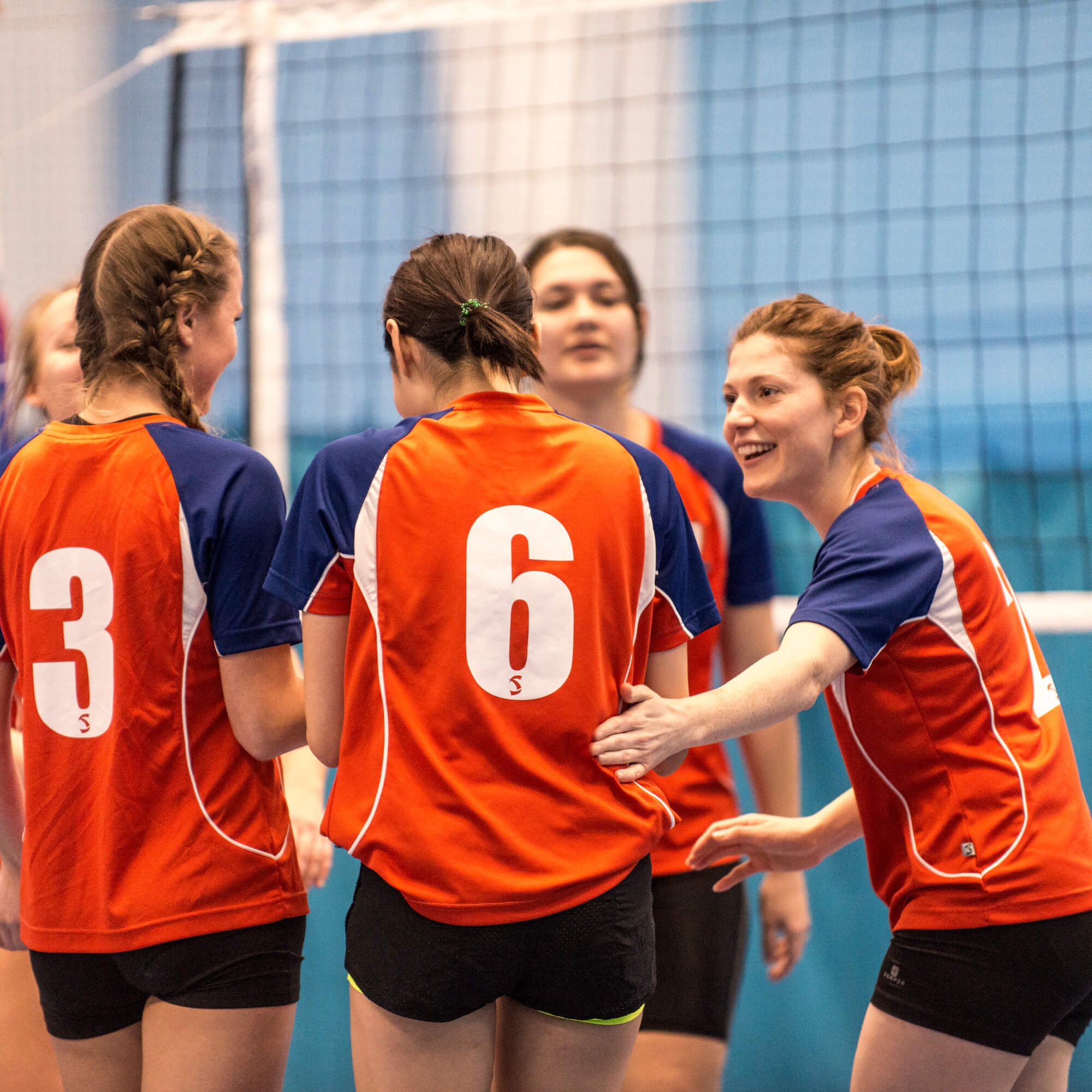 Group of female volleyball players talking and laughing in front of a volleyball net