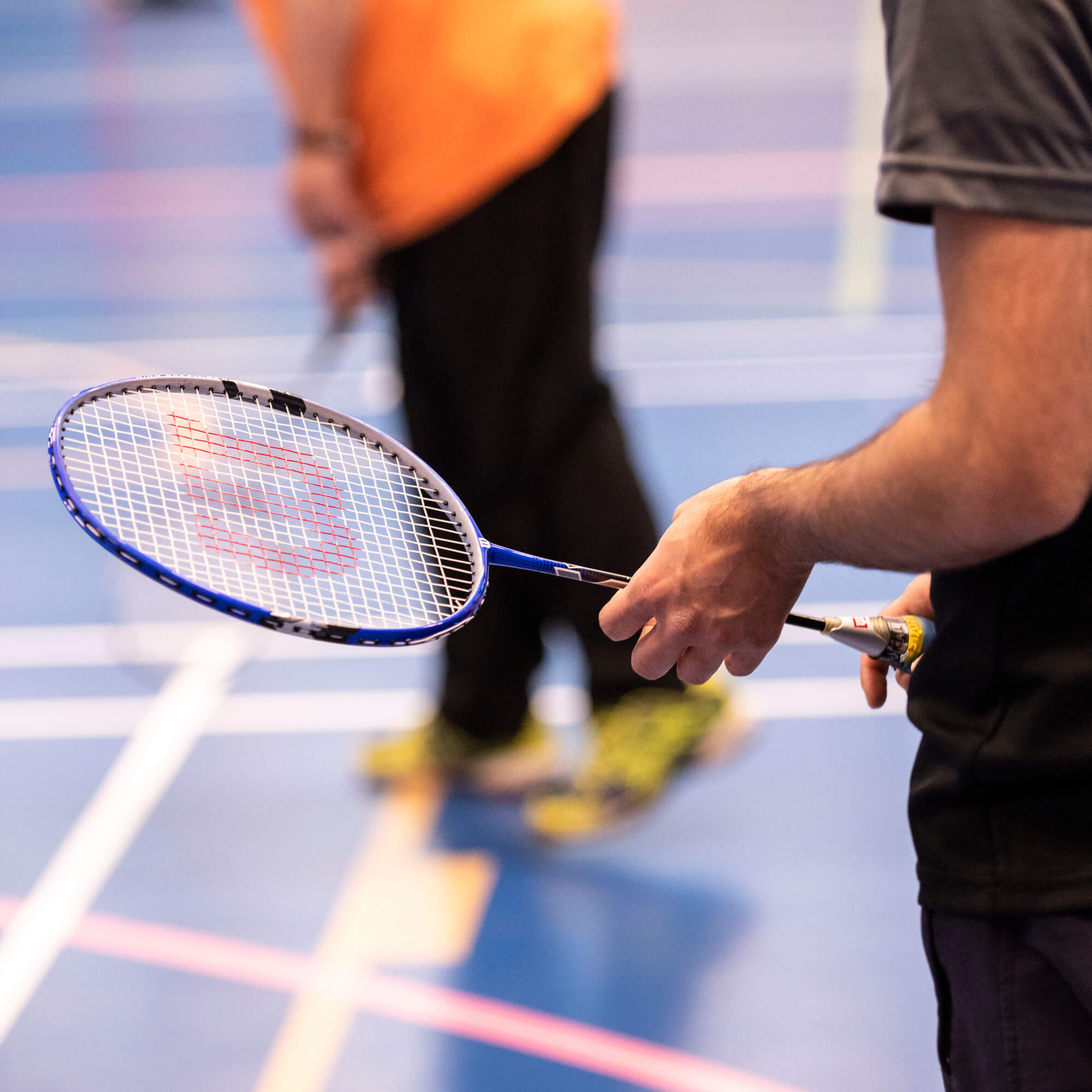 Person's arm holding onto a Badminton racket at social badminton session