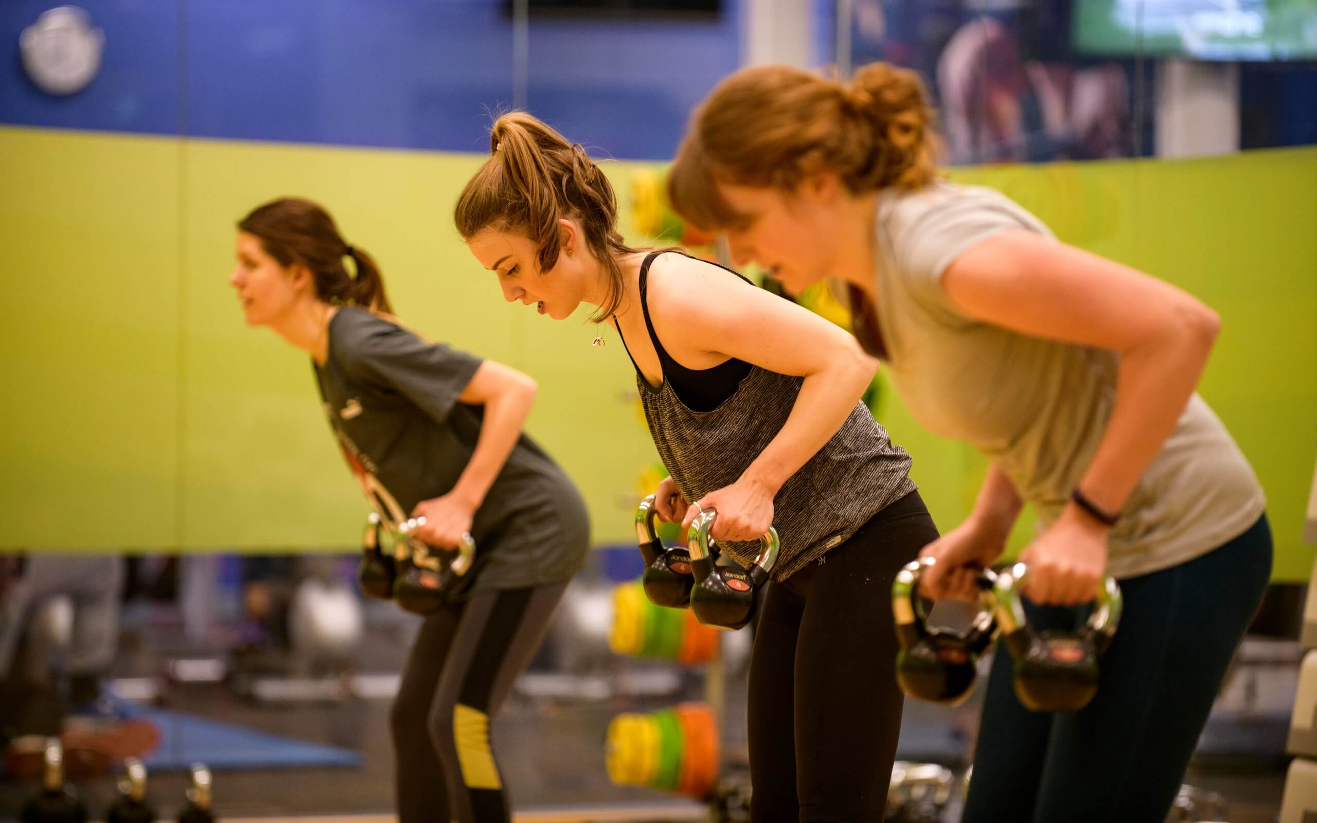 Three female students in a row lifting kettlebell weights in an exercise class