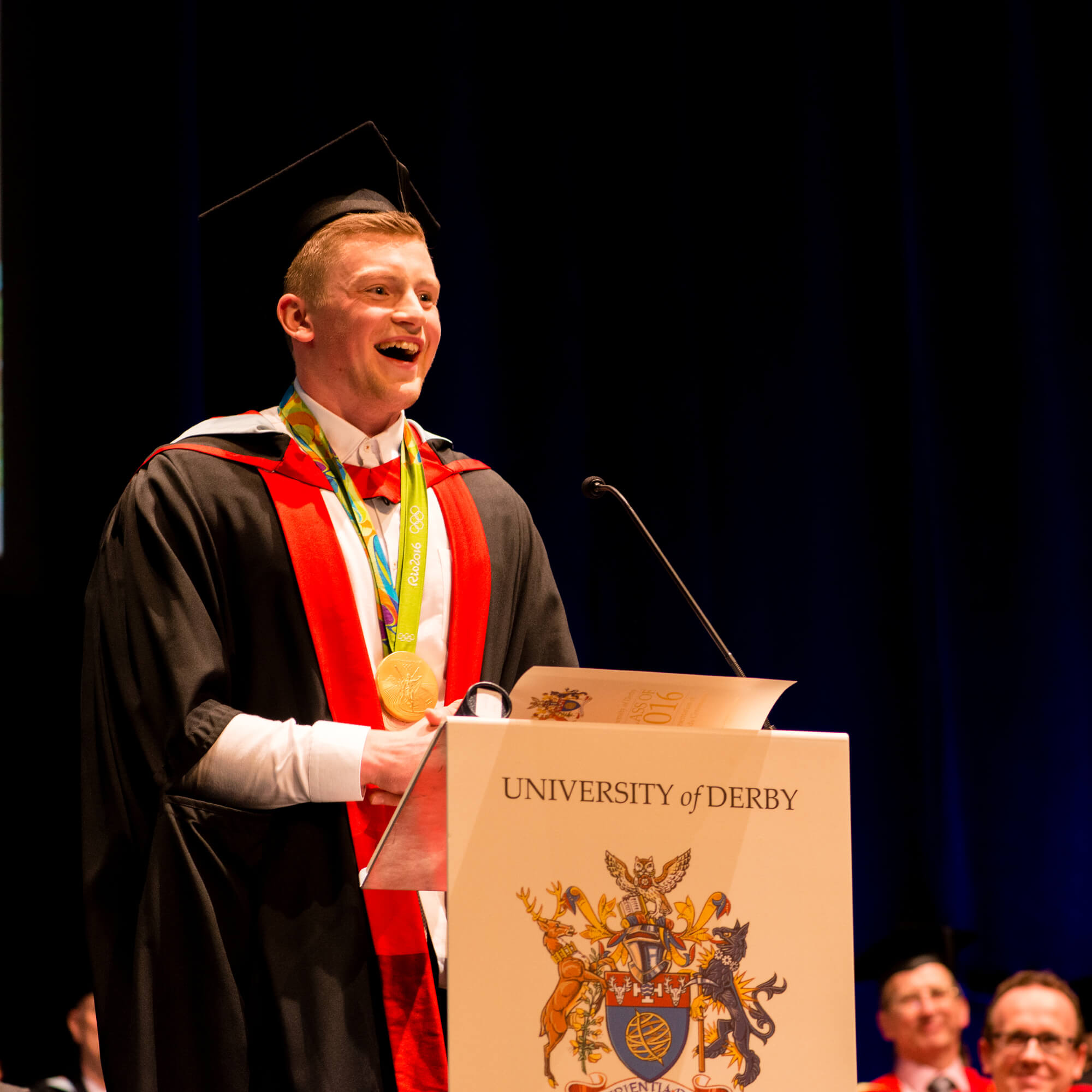 Adam Peaty speaking on podium at University of Derby Awards ceremony