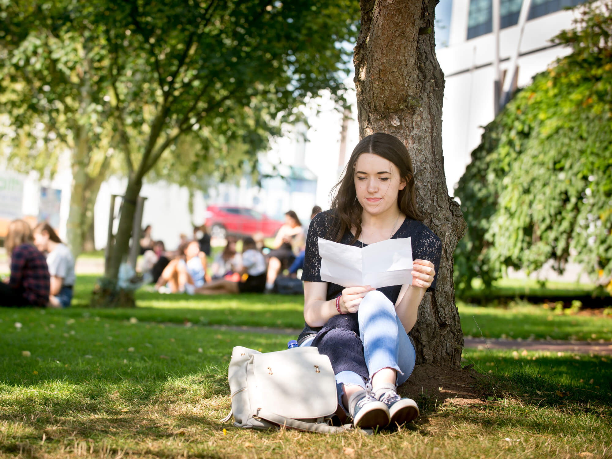 Student reading outside the university under a tree