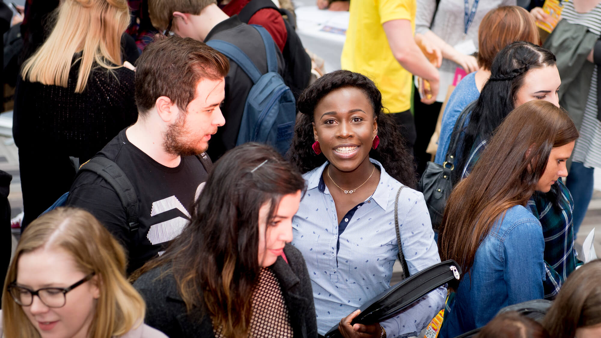 a happy BAME student in the University of Derby atrium at a Freshers event