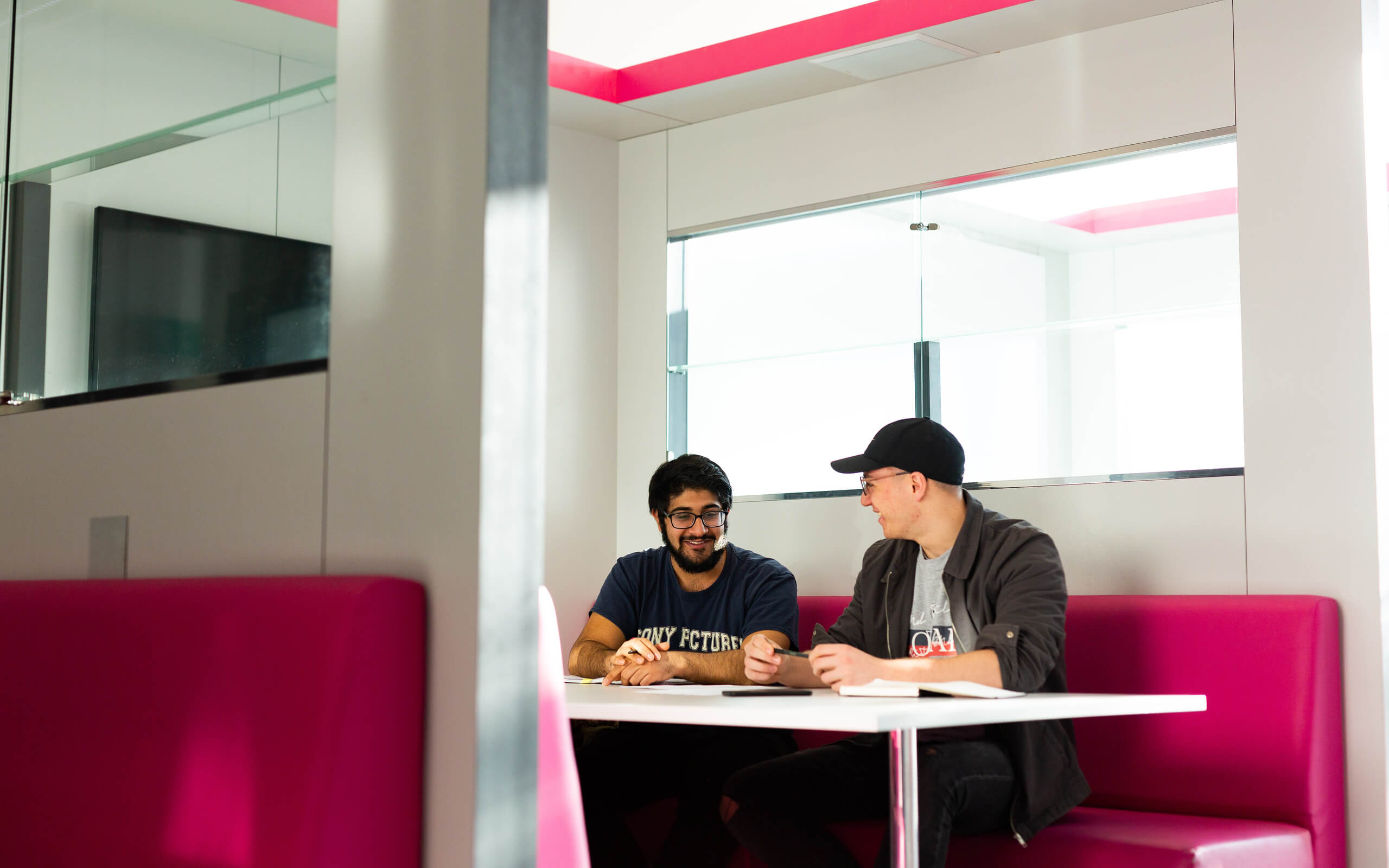 Two students studying in a study pod