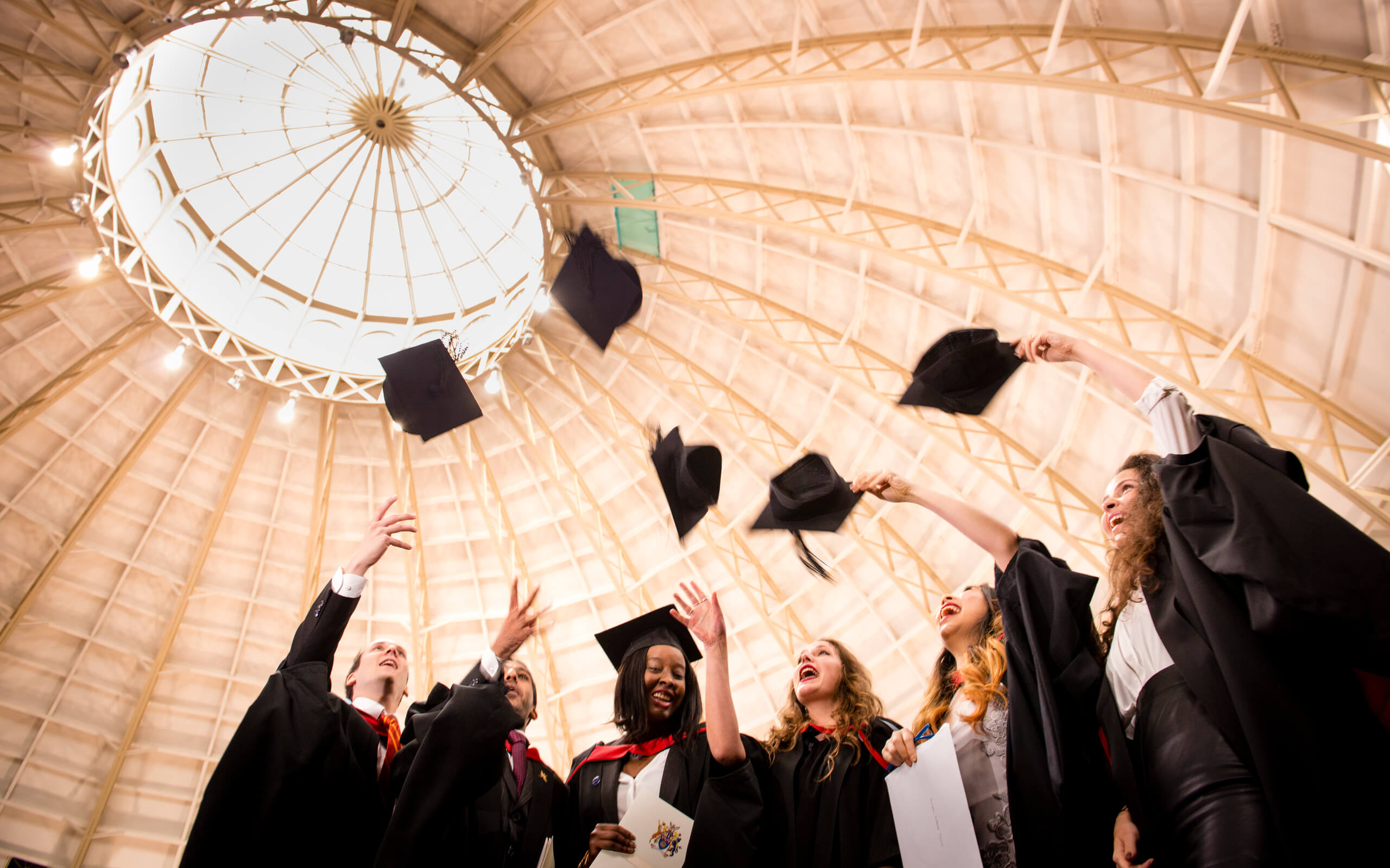 Student throwing graduation caps in the air at Buxton Awards Ceremony