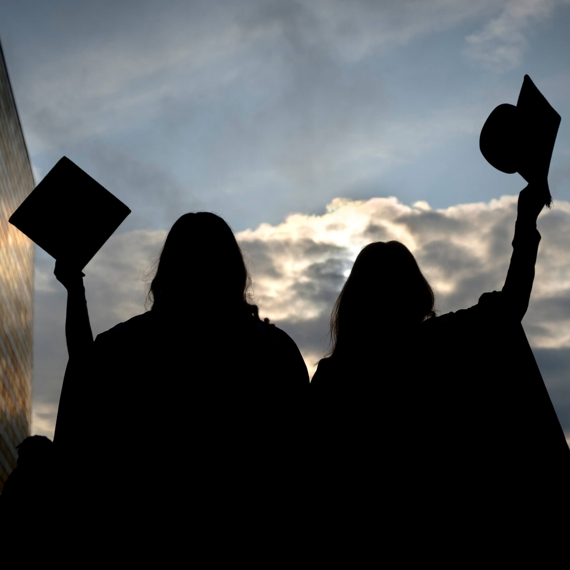Silhouette of graduates raising mortar board hats in the air
