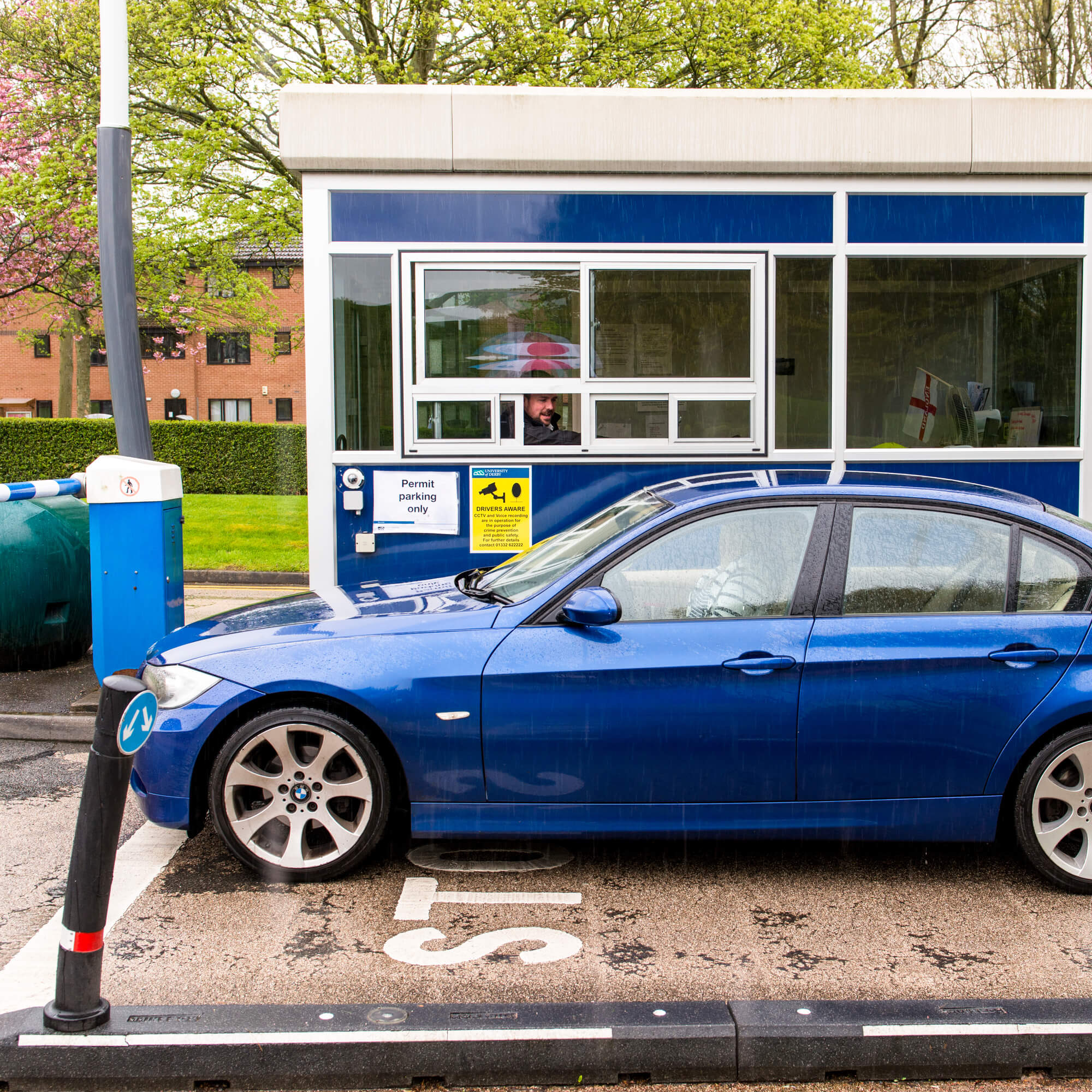 Blue car passing security barrier at Kedleston Road site, Derby Campus