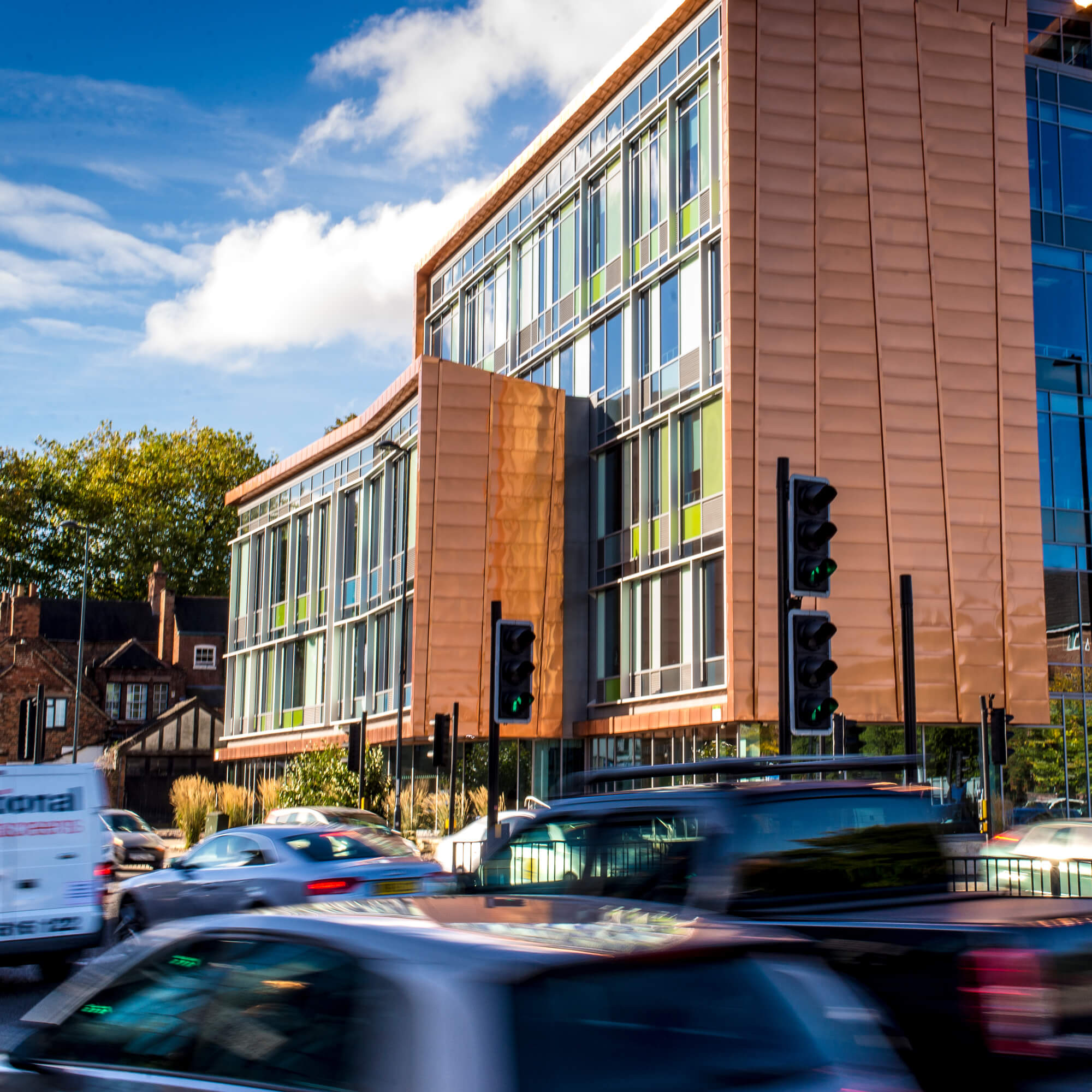 Cars driving along road next to One Friar Gate Square's copper building