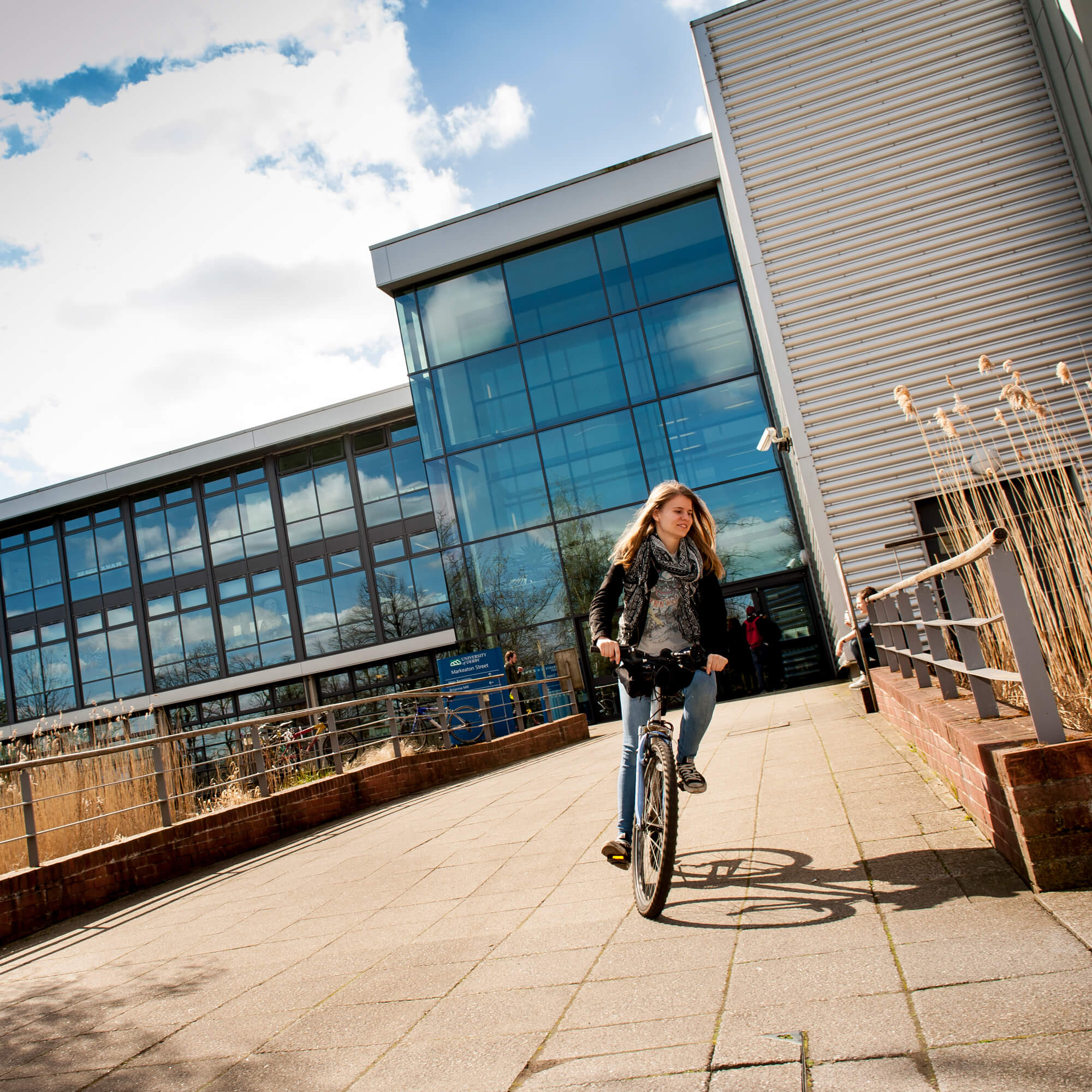 Student riding a bike at Markeaton Street site, Derby Campus