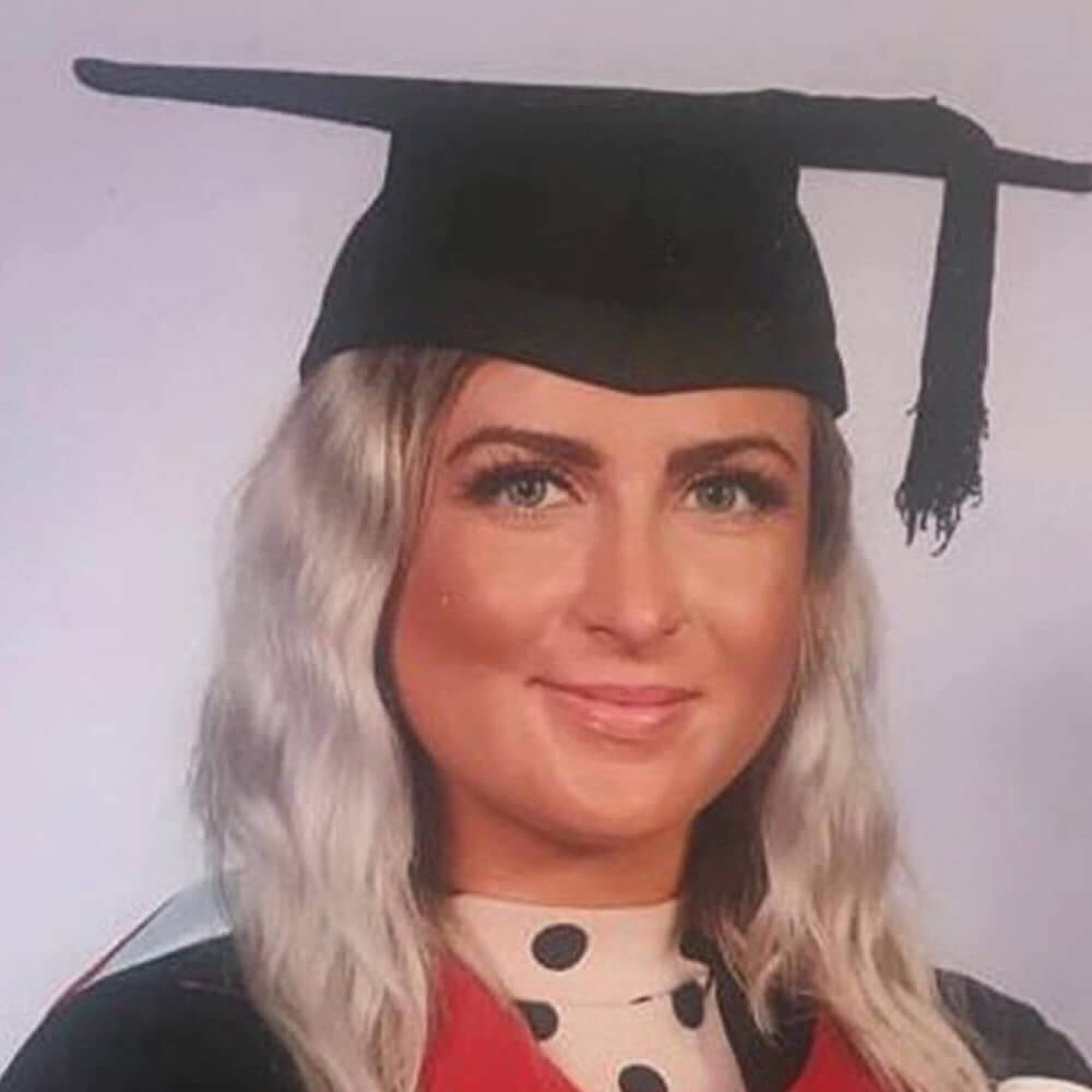 Ellen wearing a graduation gown, smiling to the camera.