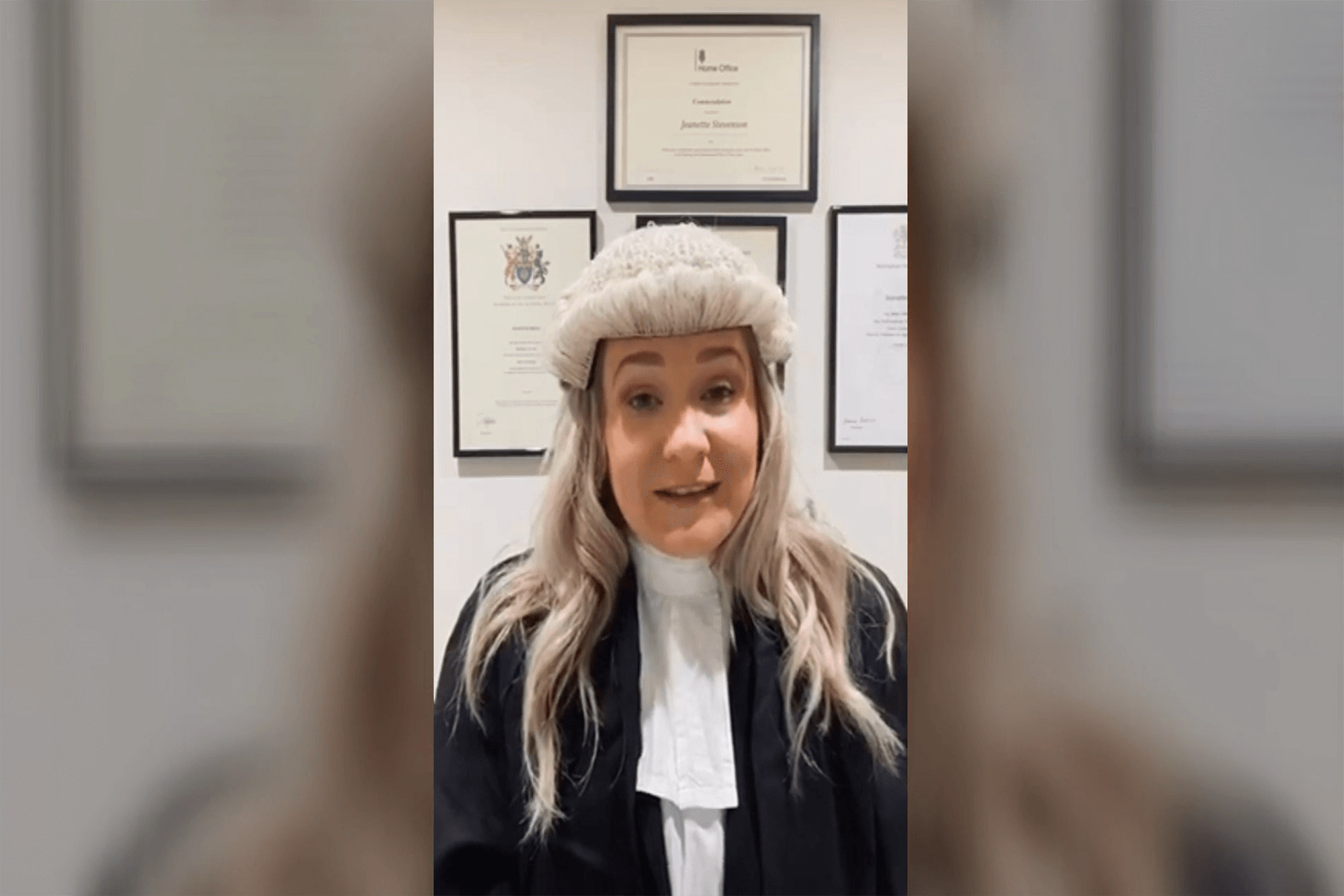 Jeanette wearing a barrister's gown, white shirt and black jacket