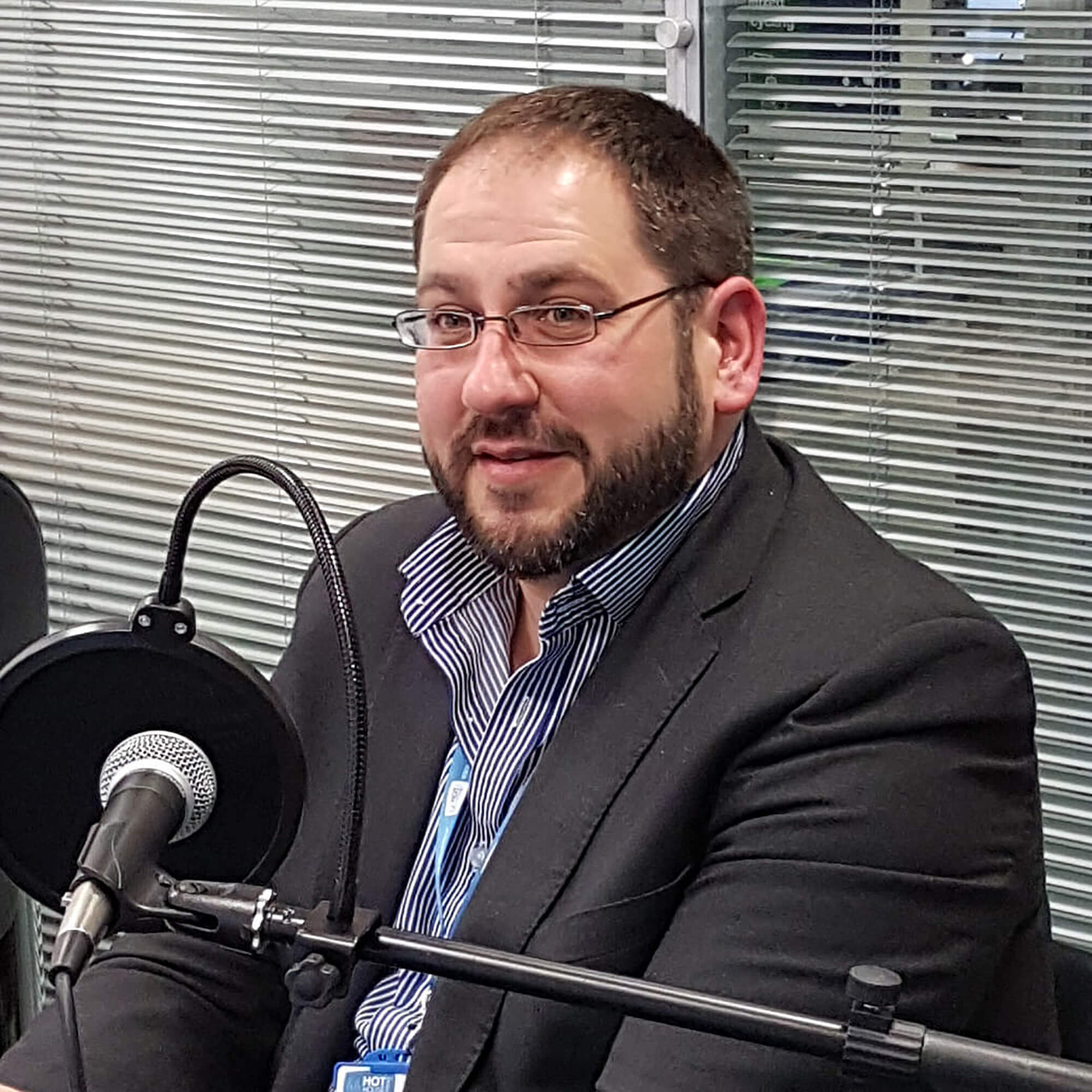 Jon wearing glasses, a blue shirt and gray jacket speaking in front of a mic at a podcast.