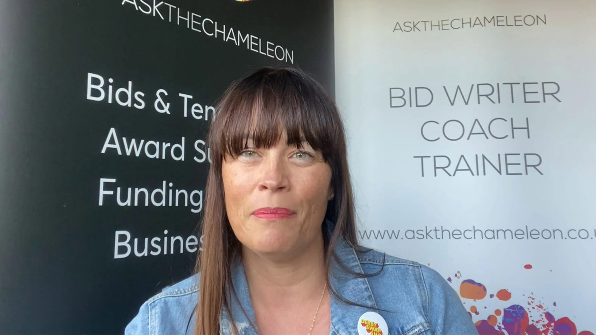 Rachel standing next to a sign that reads 'Bid writer coach trainer' and displays a link to a website: www.askthechameleon.co.uk