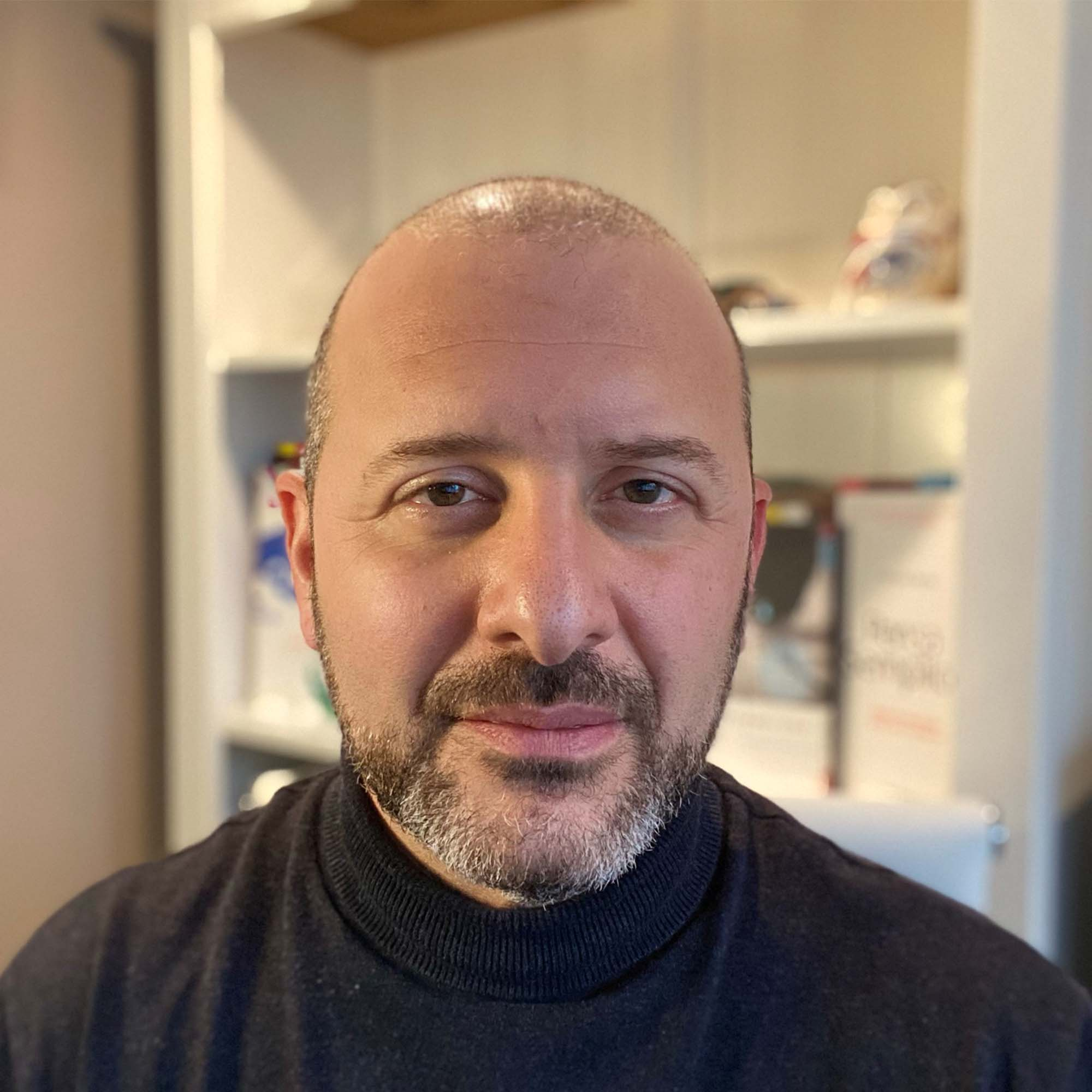 Richard wearing a black top giving a talk in front of an audience.