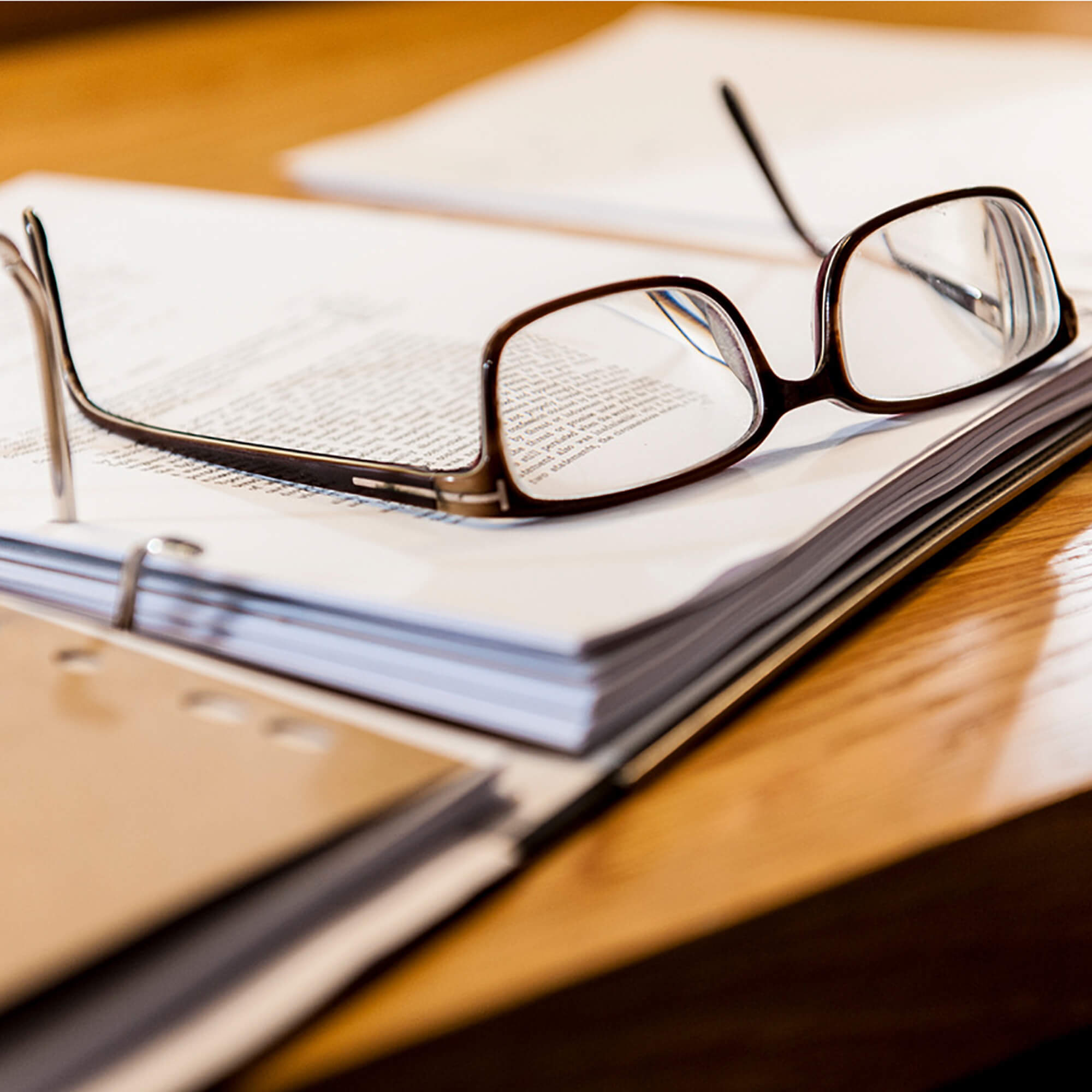 Pair of glasses positioned on an open notebook.