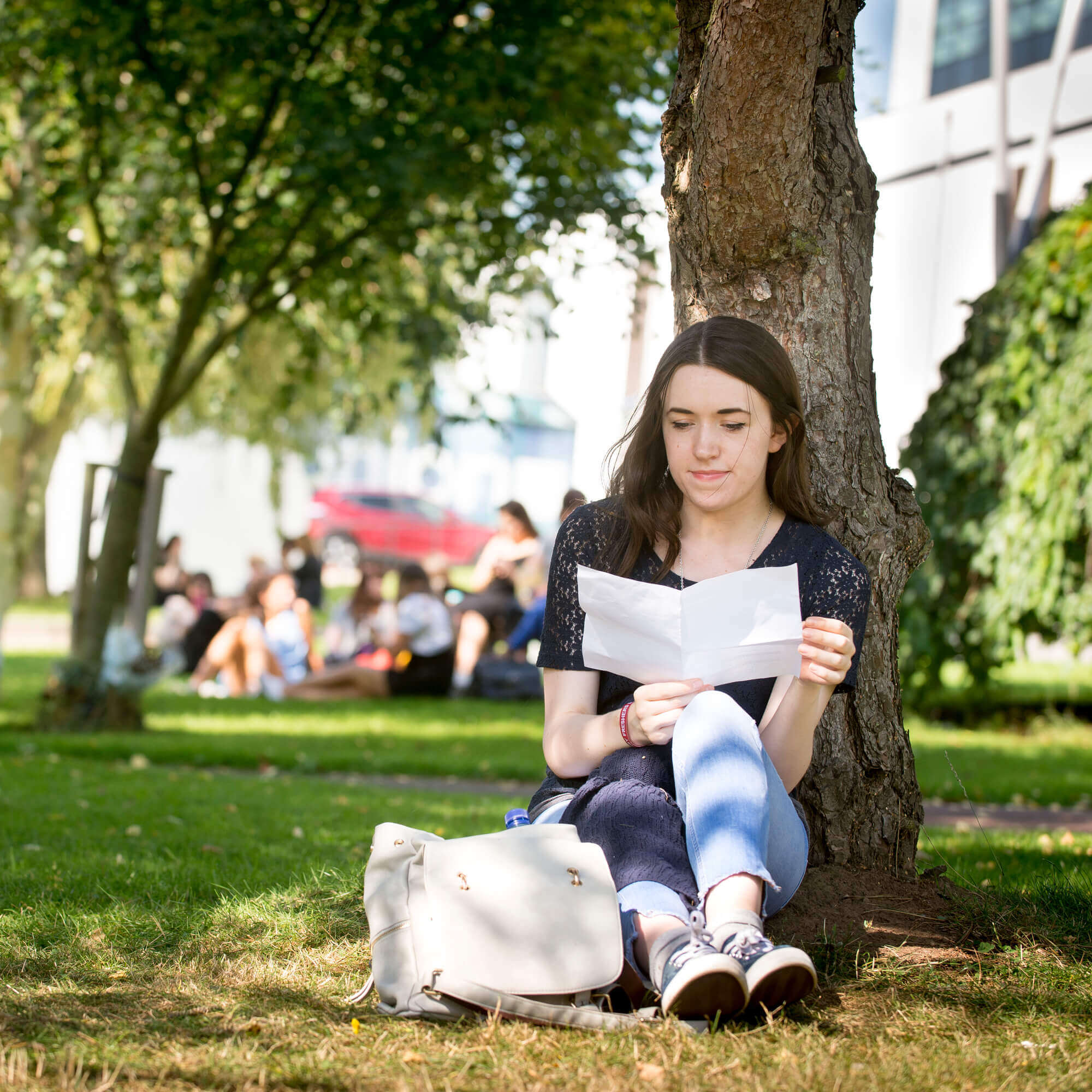Person sitting under a tree reading a book