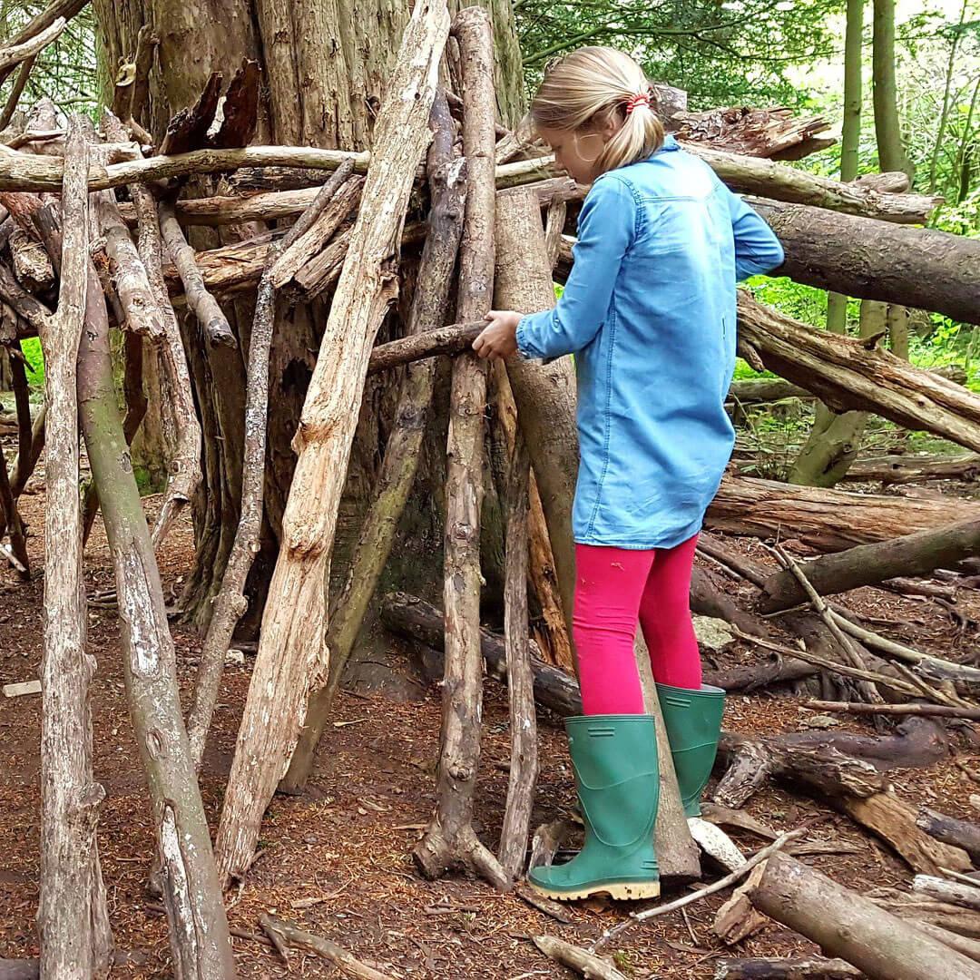 Girl building den in woods