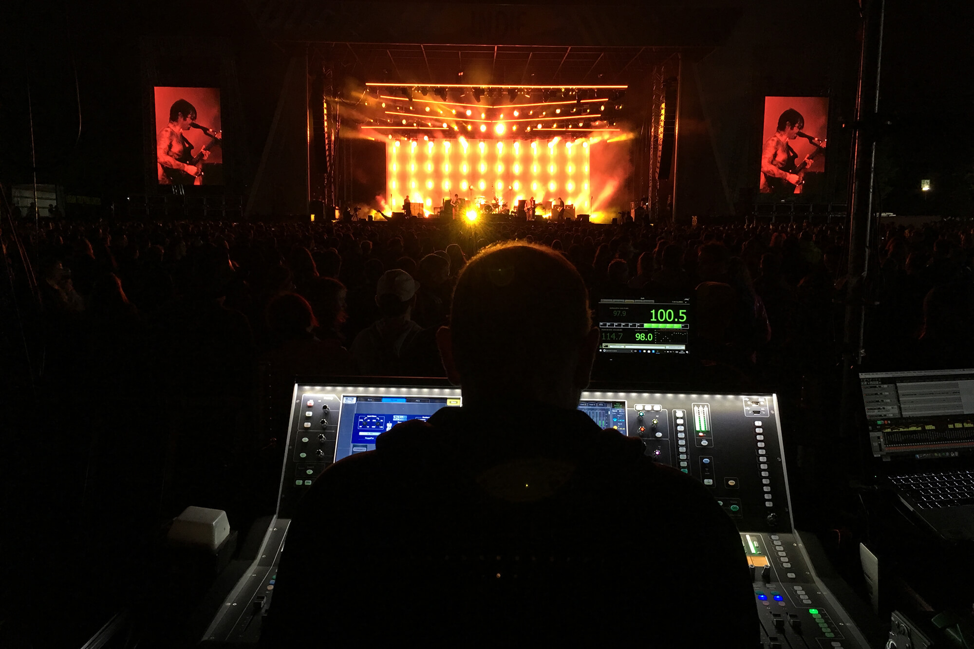 An engineer operating a sound and light desk at a live event.