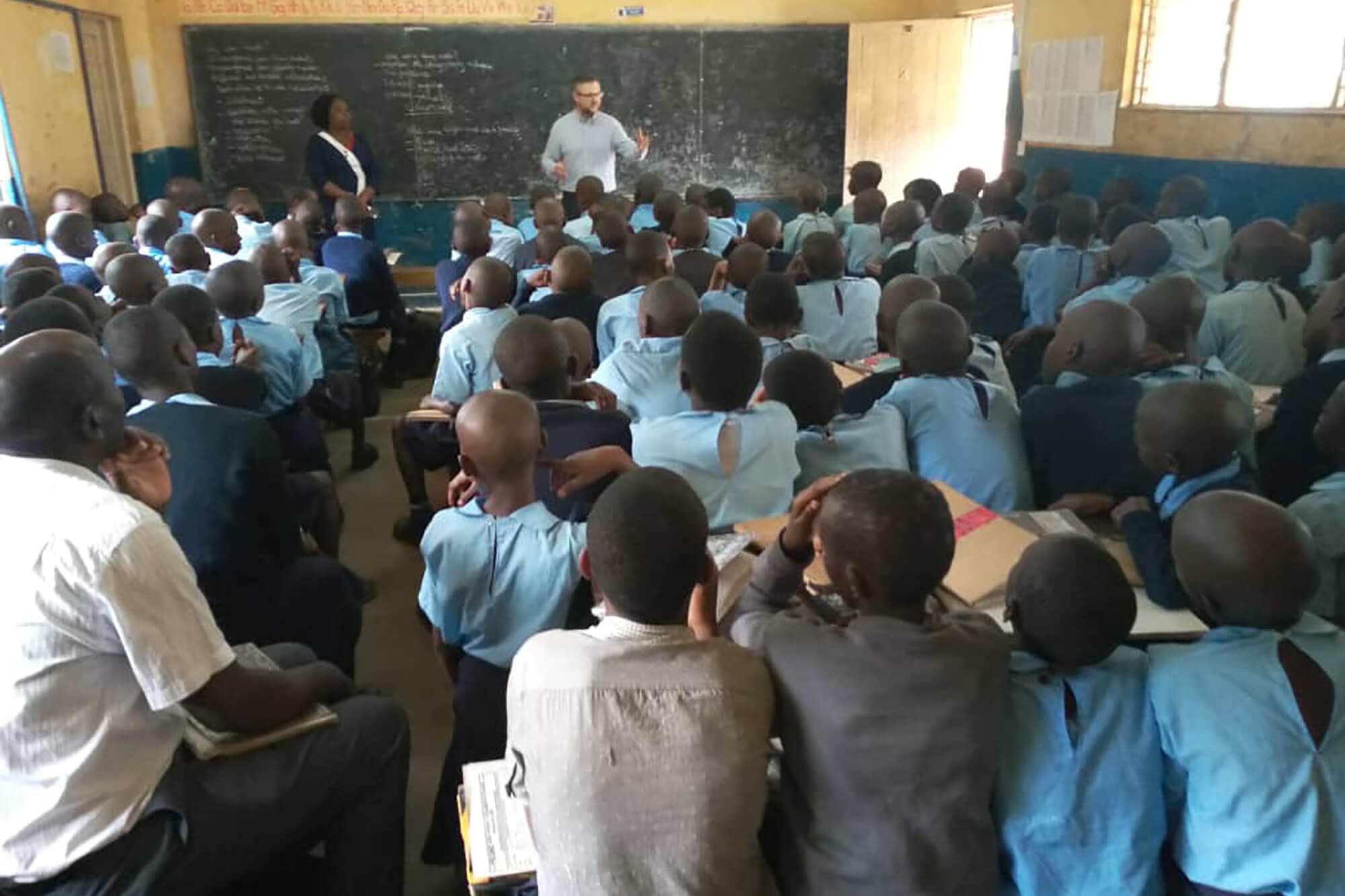 A person standing in front of a blackboard teaching a large class of African children.