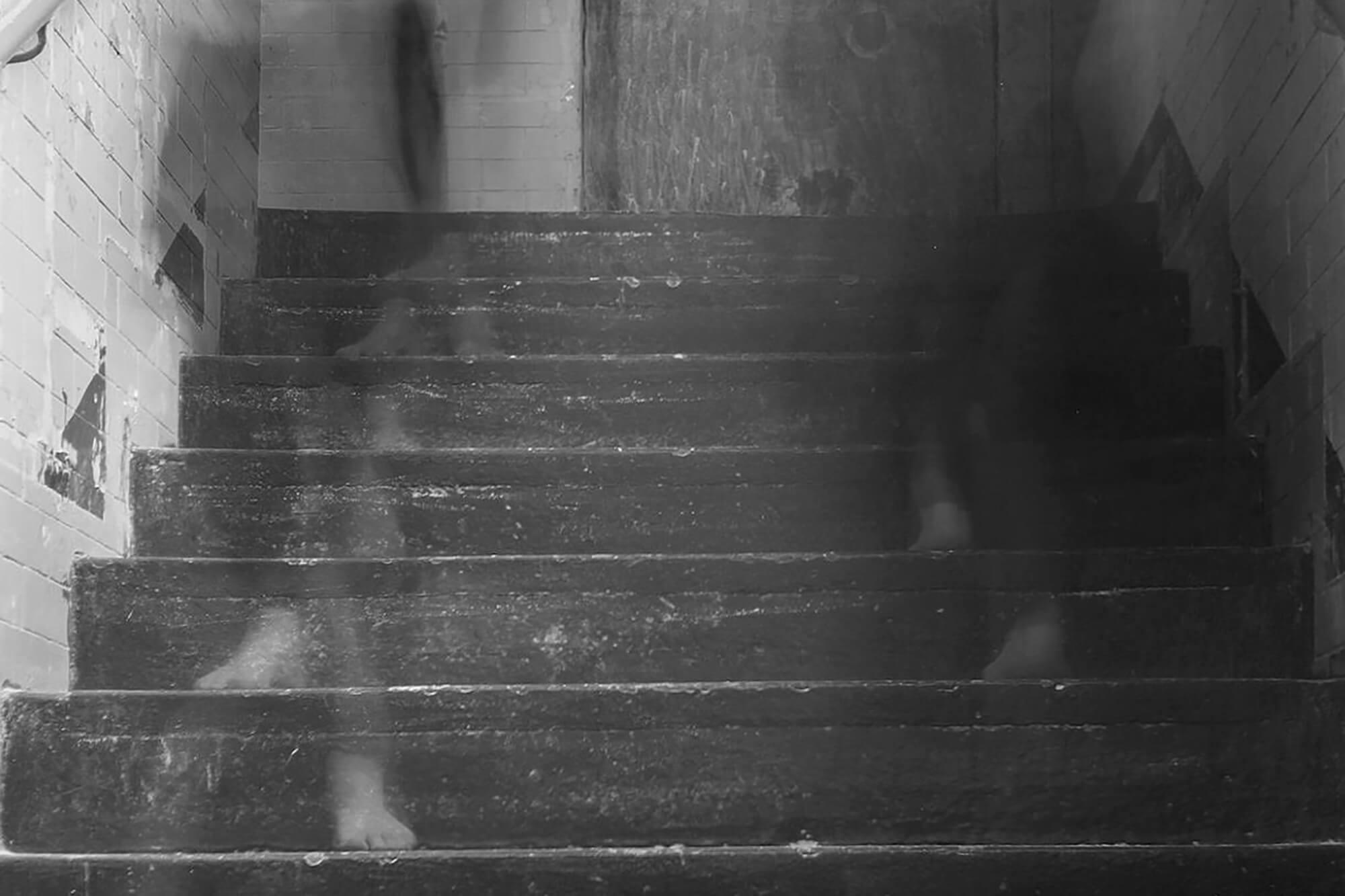 A long-exposure photograph with ghost images of people walking up and down steps