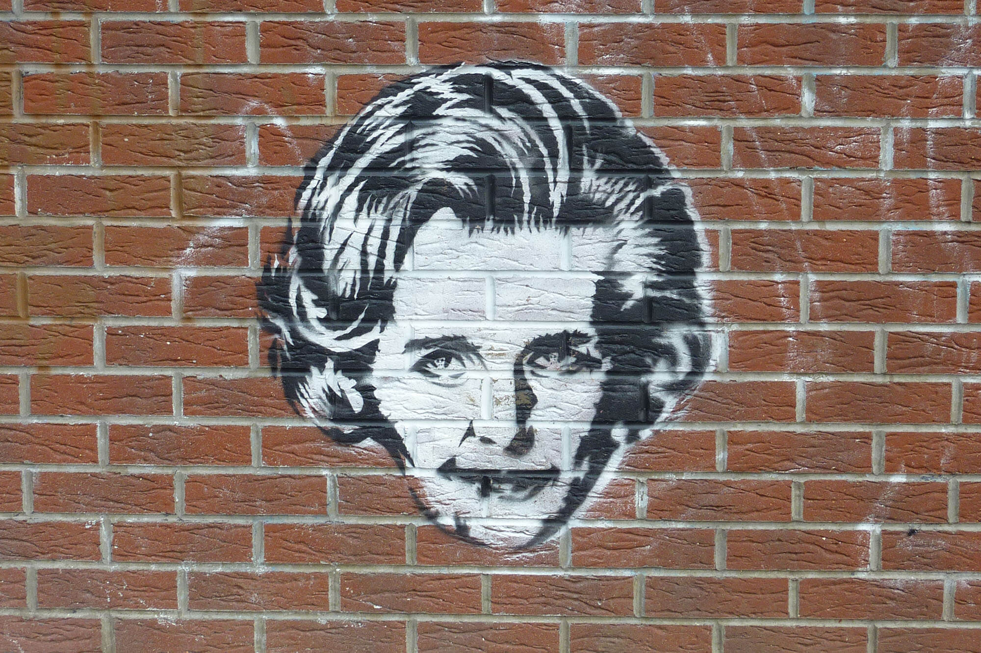 Graffiti of Margaret Thatcher's head on a wall.