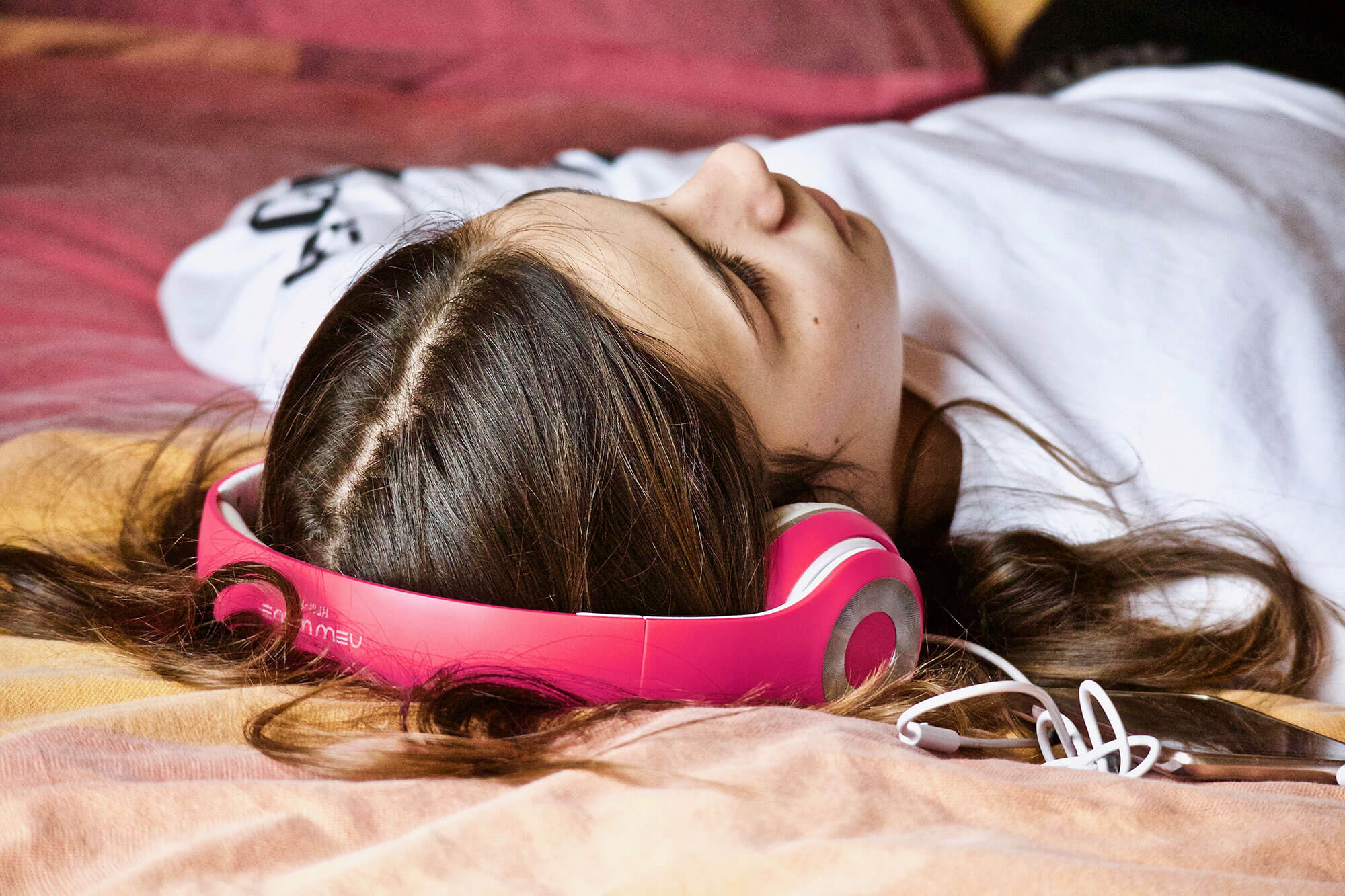 Girl laying down with headphones on