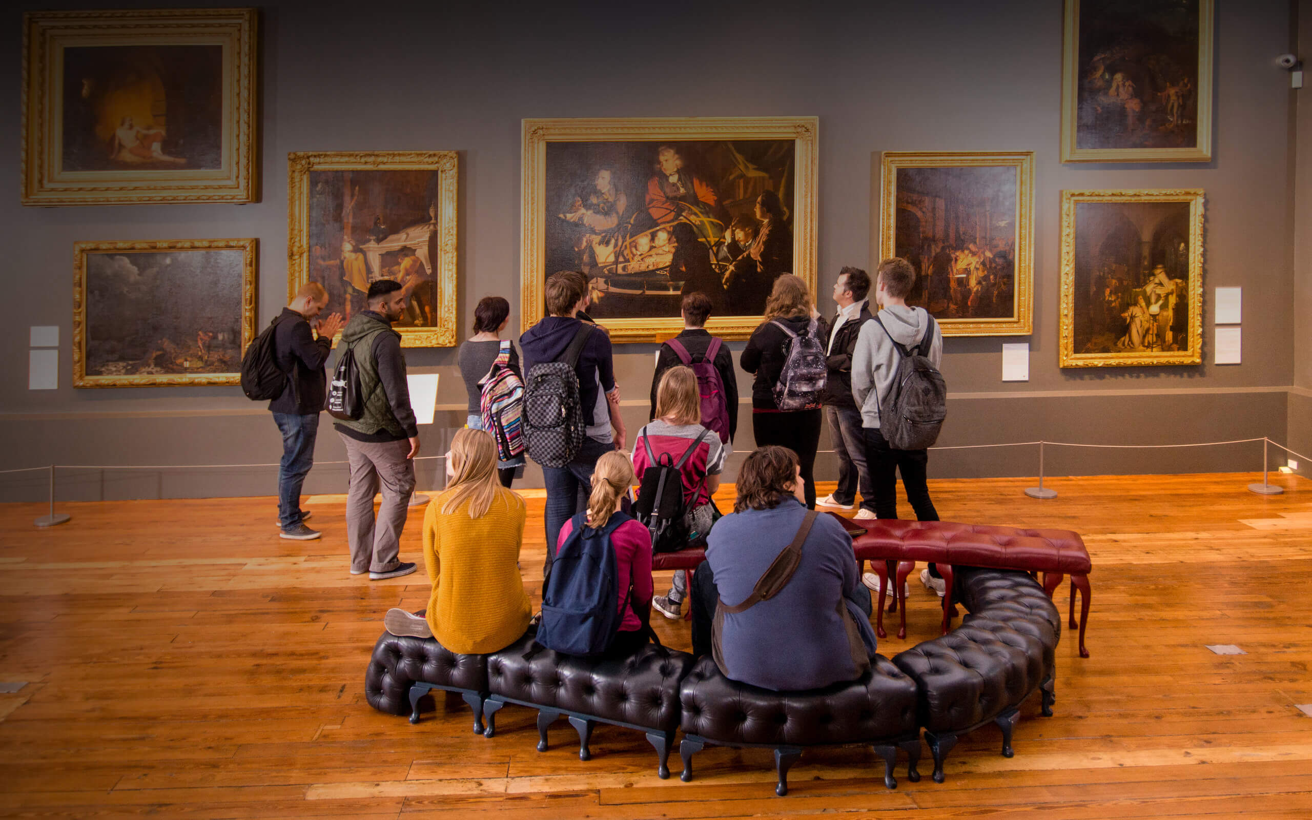 Visitors to Derby Museum and Gallery look at Joseph Wright's painting A Philosopher Lecturing on the Orrery