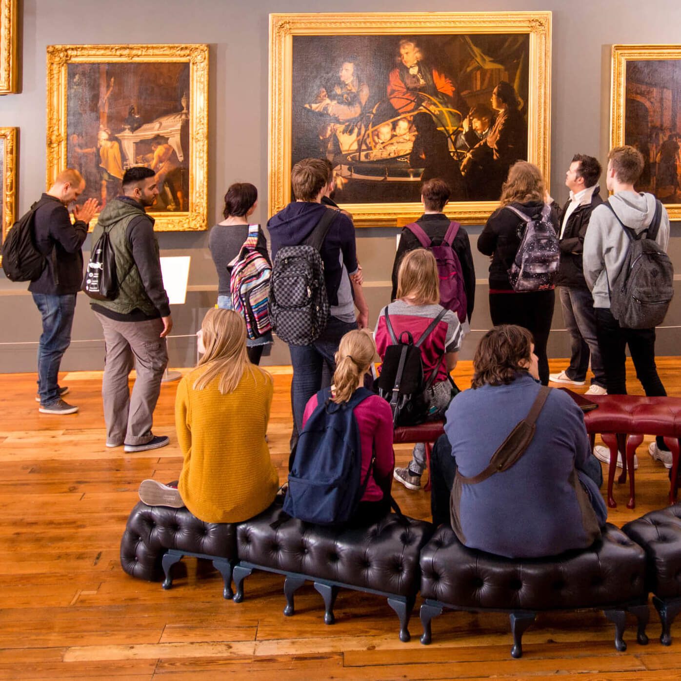 Visitors to Derby Museum and Gallery looking at Joseph Wright's painting A Philosopher Lecturing on the Orrery