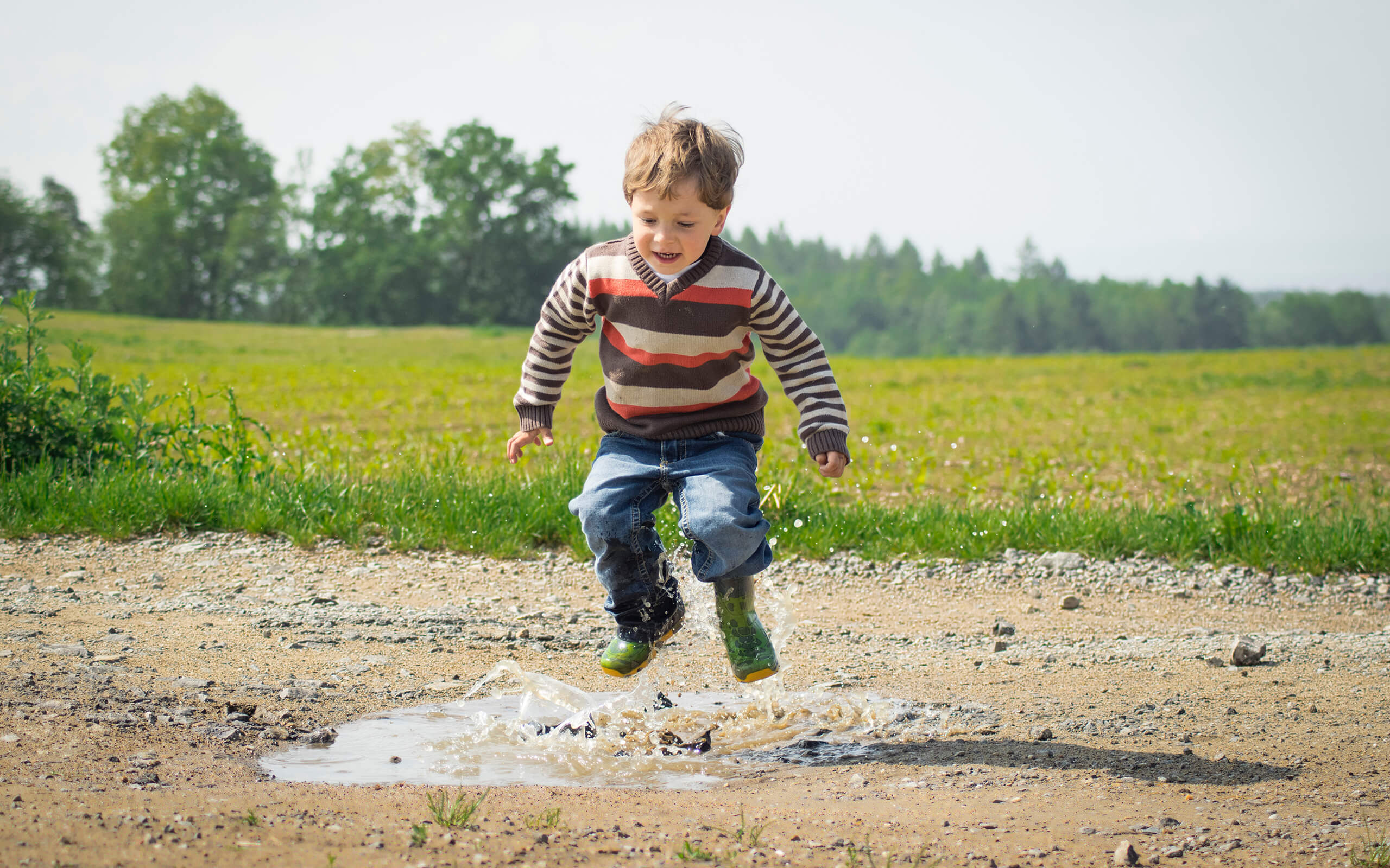 a child jumping in a puddle