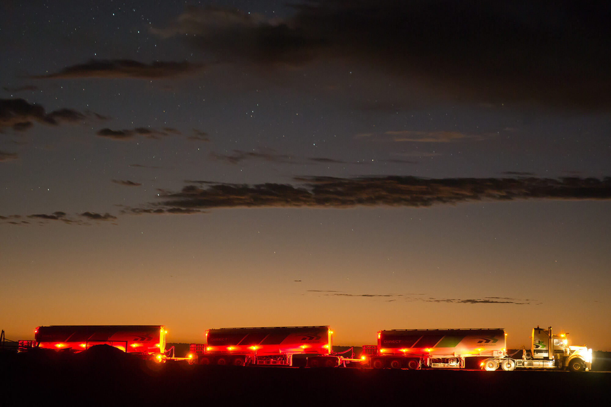 a road train crosses the claypan in the middle of the night