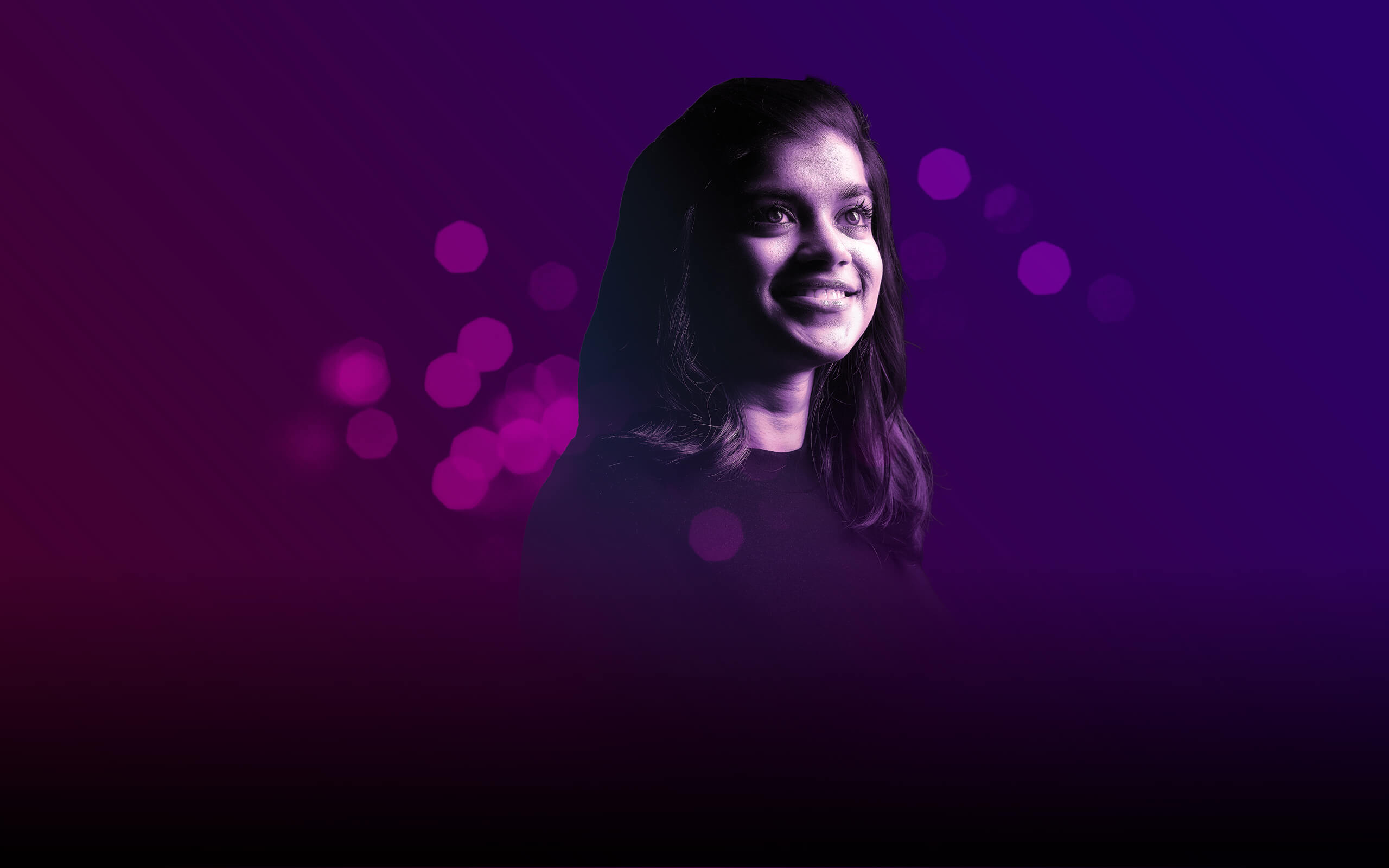 Side-on portrait of a young student with purple bokeh lights in the background