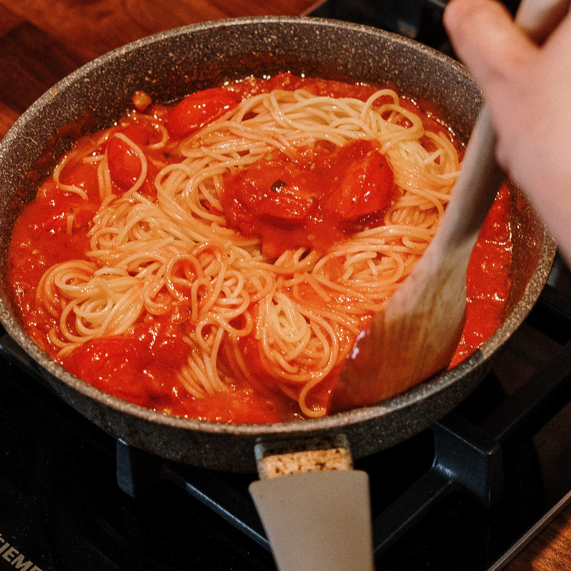 pasta and tomatoes being cooked in a pan