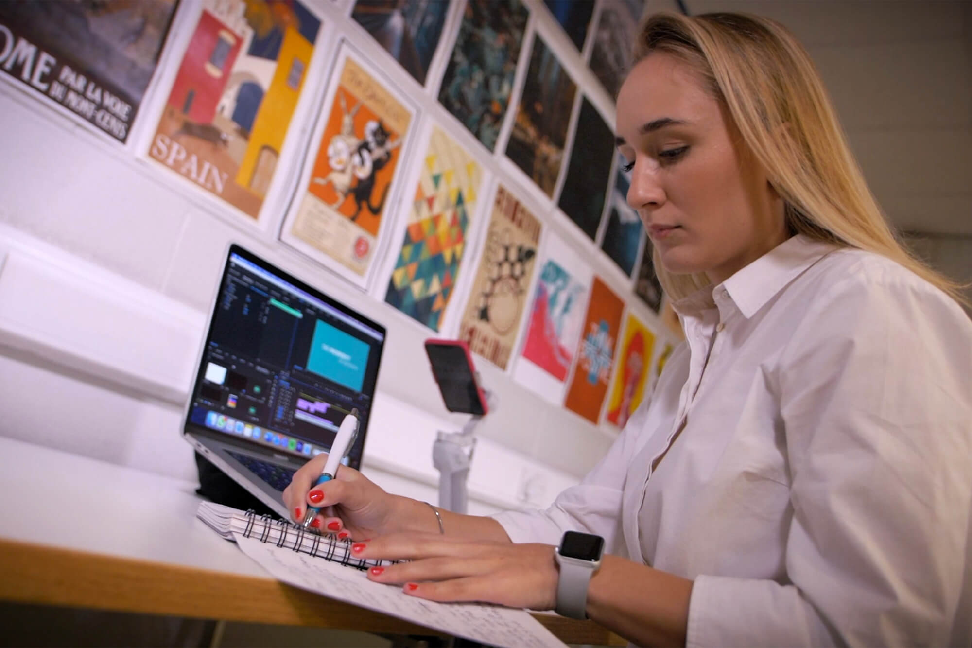 Barbora Horackova at work, making notes. A laptop and mobile device sit on a desk. Graphic design images on the walls