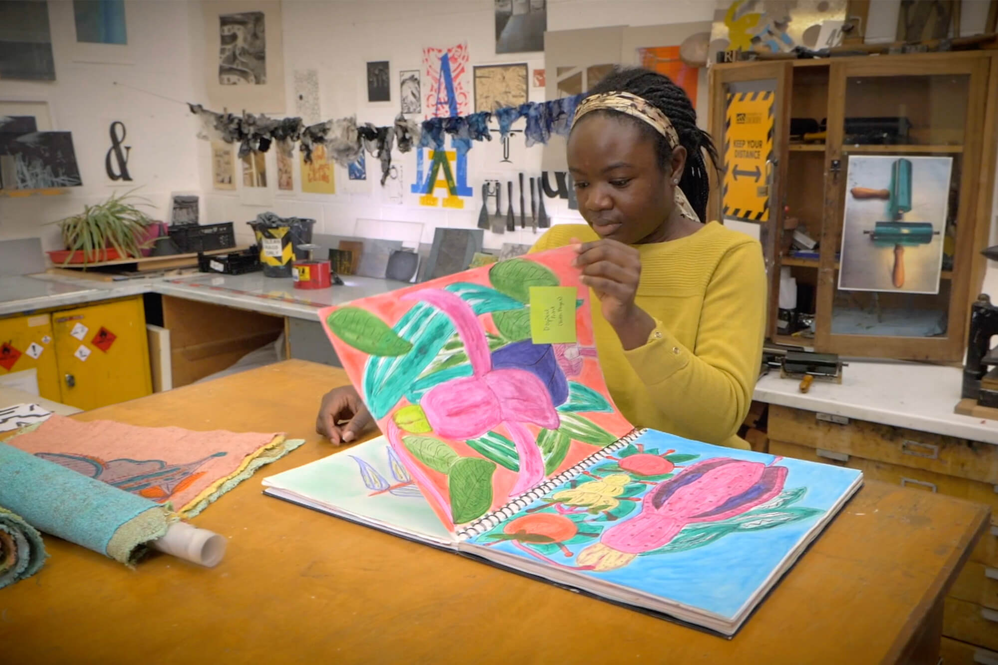 Jessica Boateng looks through a book of colourful designs