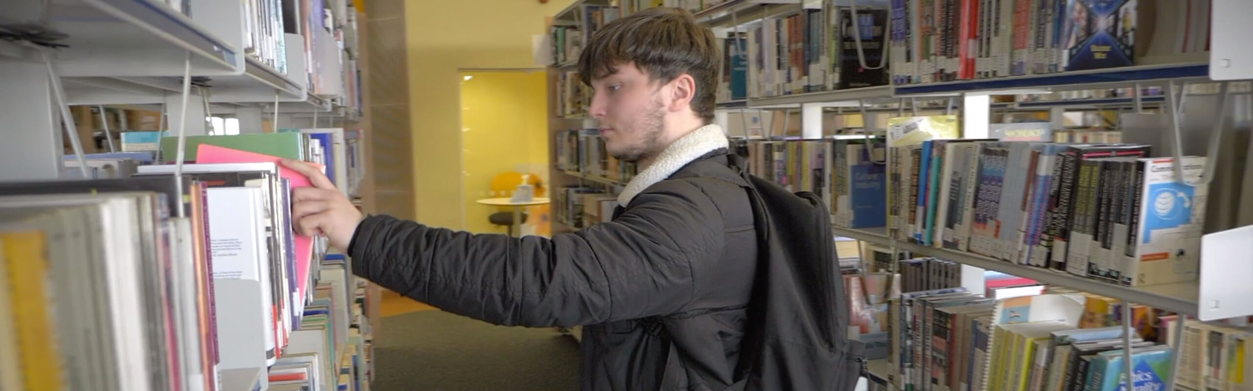 Tom Berrington selecting a book in the library