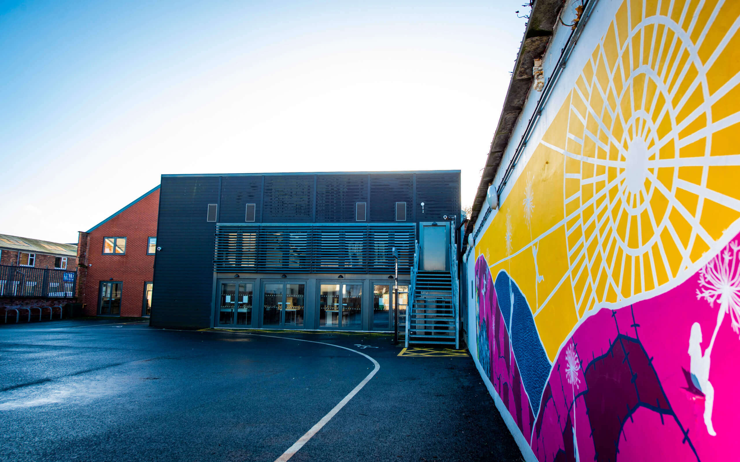 The Fashion and Textiles Centre at the University of Derby, next to a painted mural on a wall