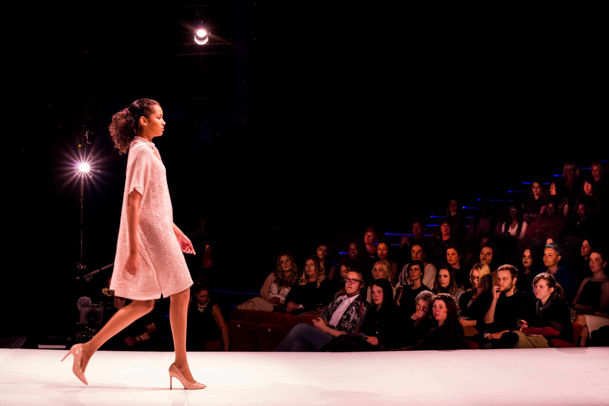 A model walking on a runway during a fashion show at Derby theatre