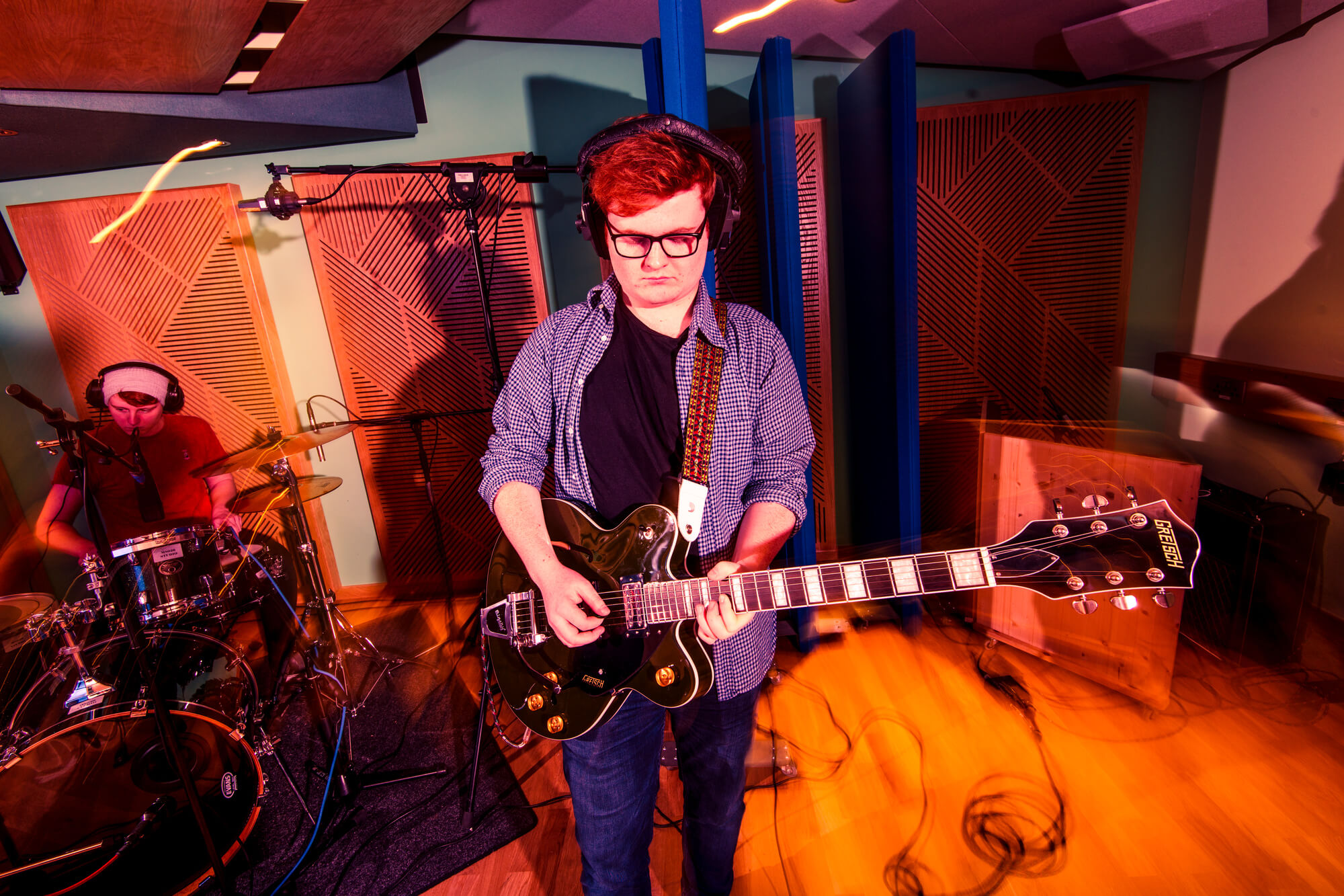 A student playing guitar in a recording studio at Markeaton Street
