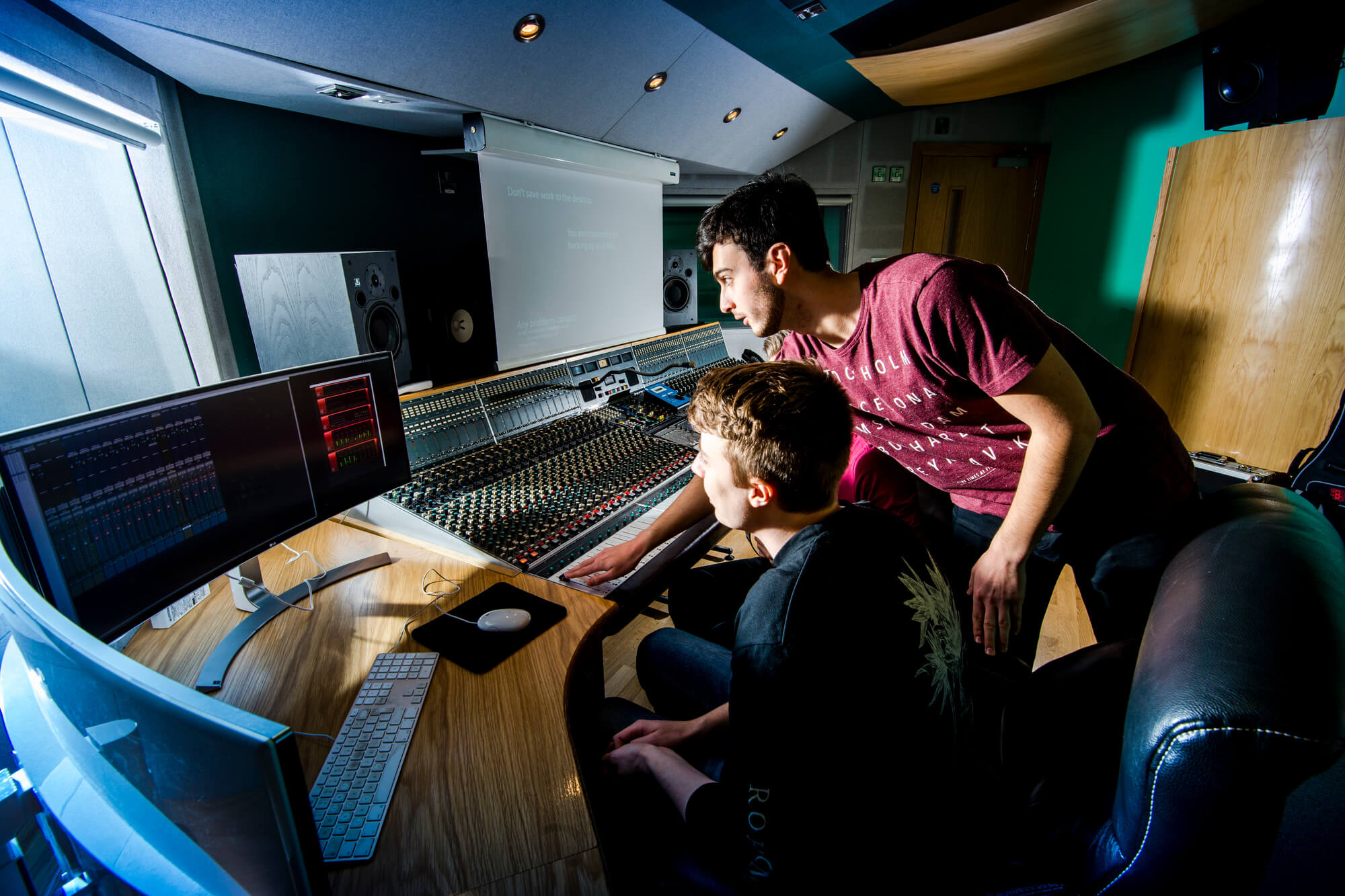 Two students working on sound equipment in the music studio